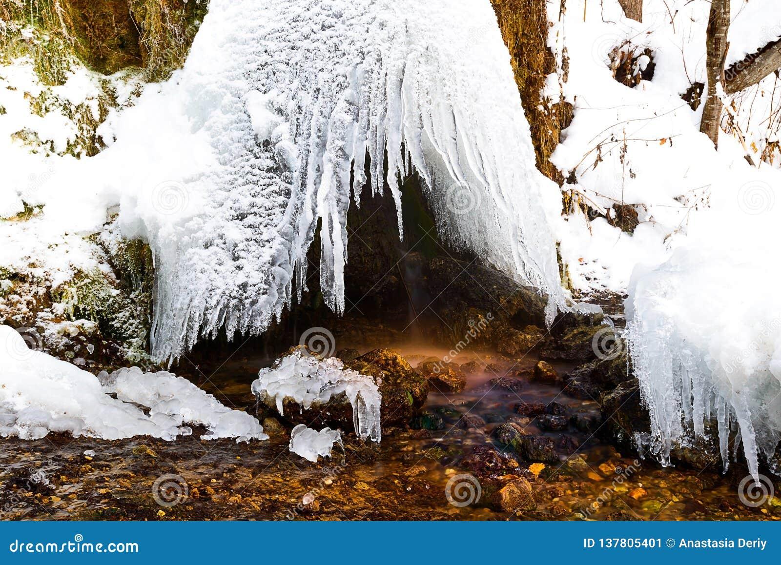 La cupola del ghiaccia la cascata Raduzhny, da cui flussi piccoli di corrente, Russia
