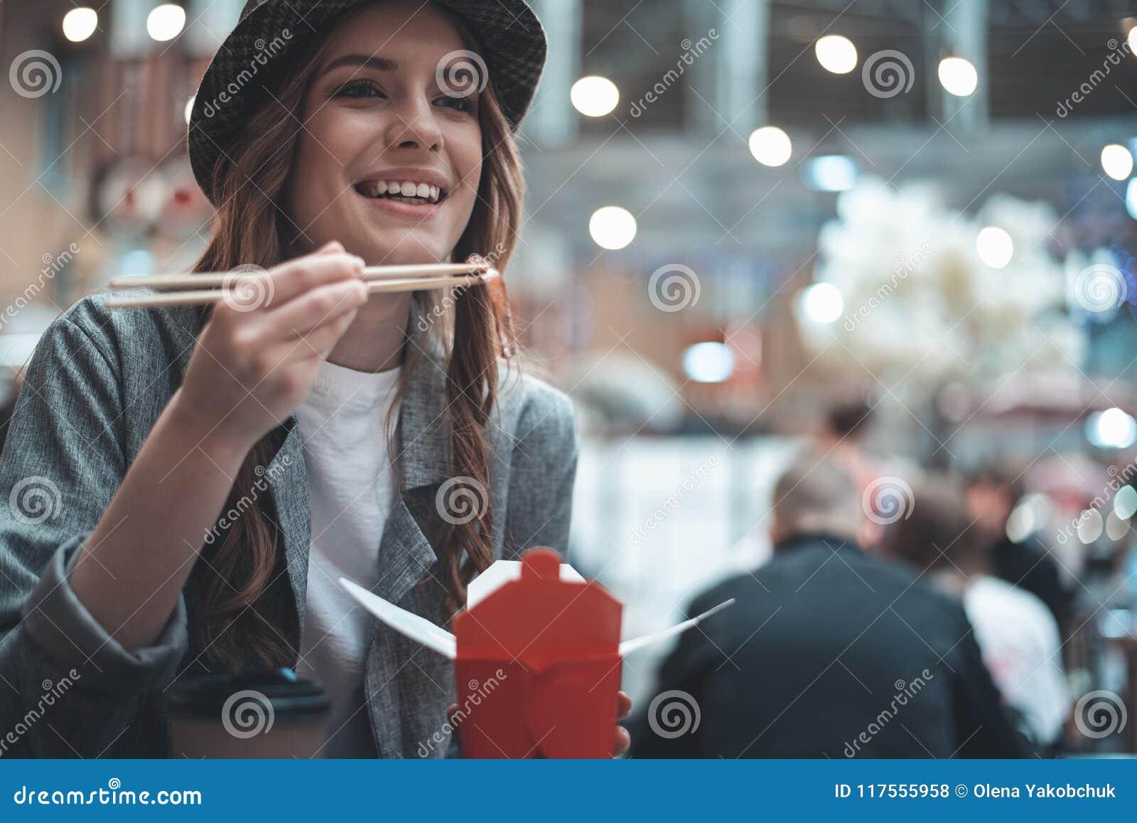 La dame gaie mange les repas asiatiques