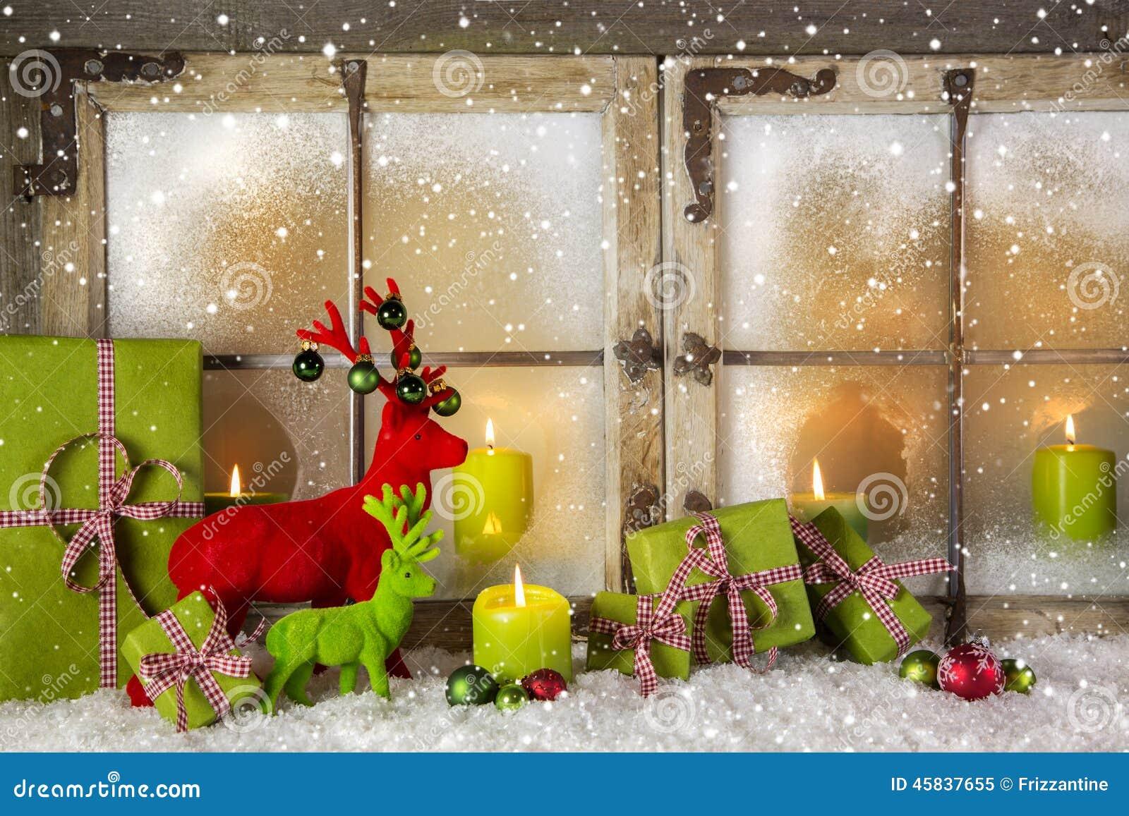 La decoración festiva de la ventana de la Navidad en verde y rojo con presen