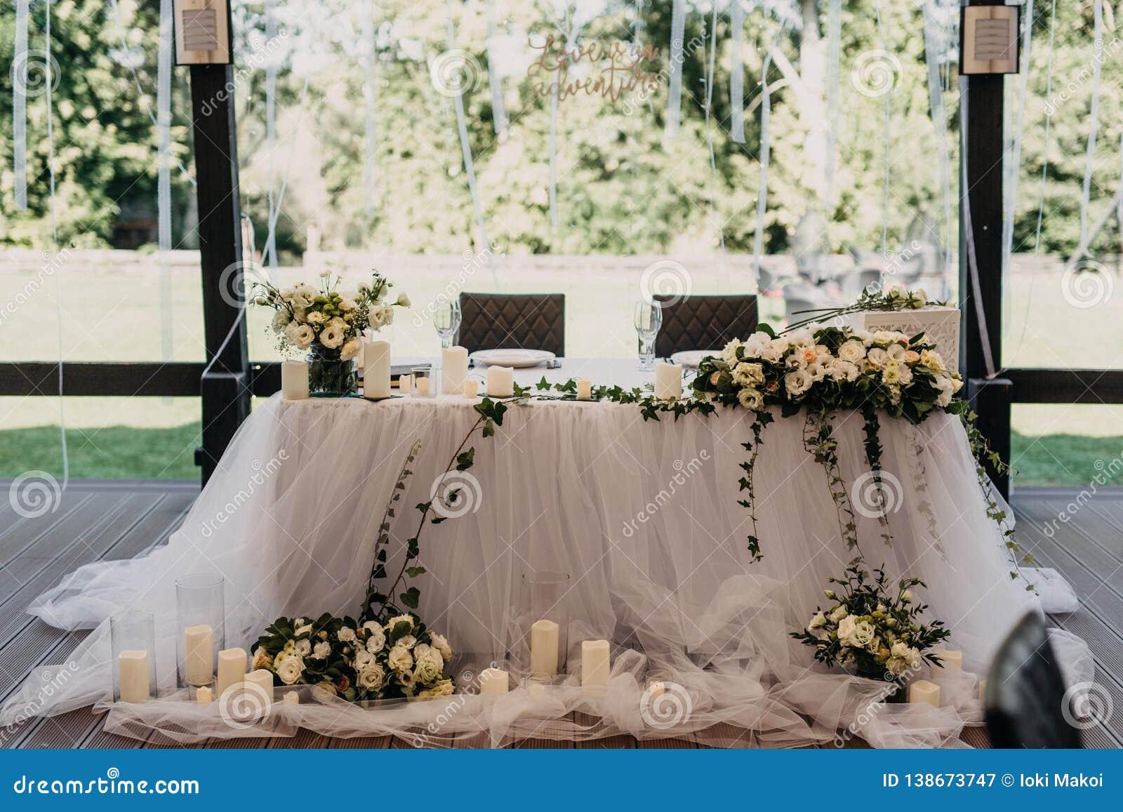 La decoración que se casa en terraza abierta del restaurante con las rosas blancas y las velas