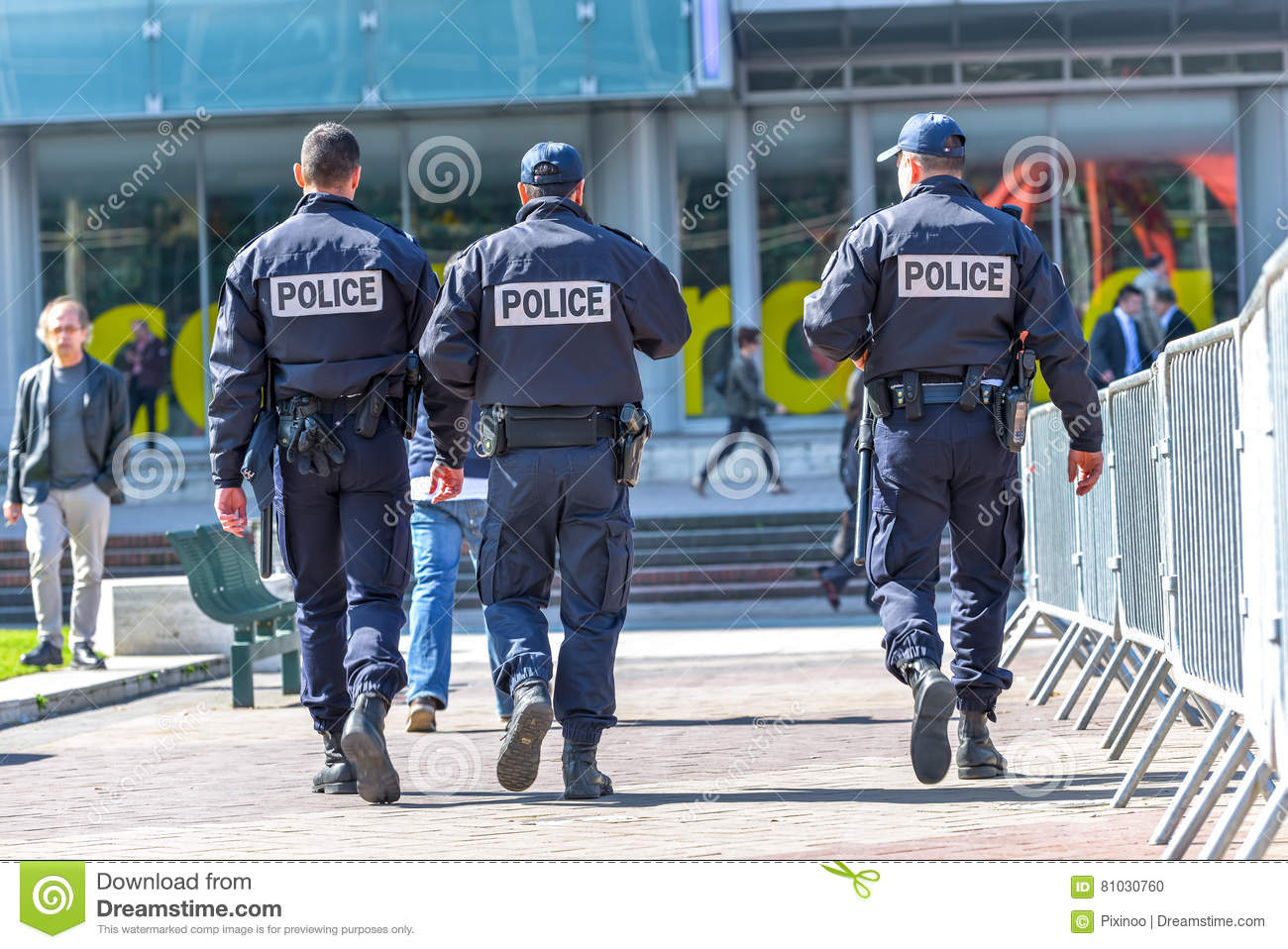La defense, France- April 10, 2014: Back view of tree police officers walking in the center of La defense, great business block ne