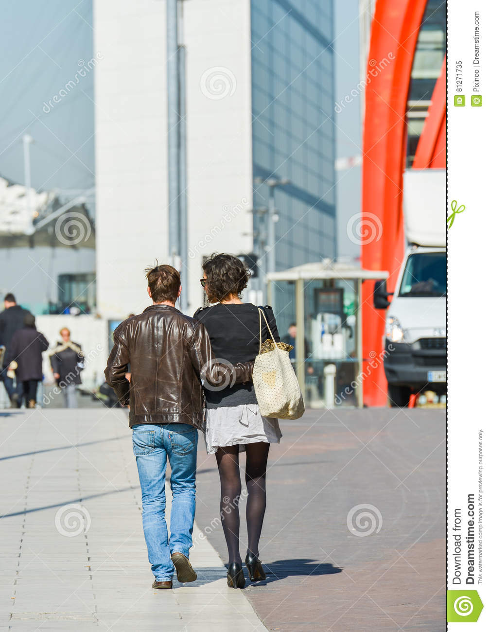La defense, France- April 10, 2014: Stylish couple walking in a street. The man is wearing blue jean s and the woman short grey sk