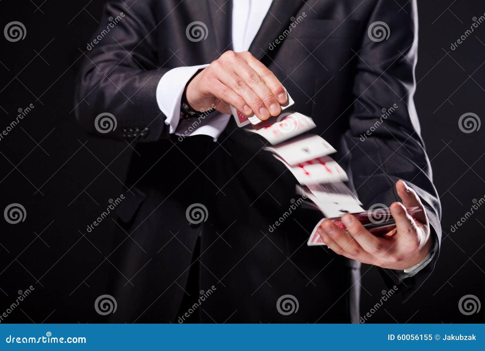 La demostración joven del mago engaña con tarjetas de la cubierta Cierre para arriba