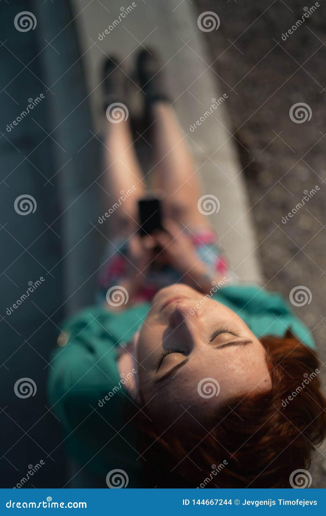 La descripción de una mujer joven utiliza el teléfono en un parque del palacio que se sienta en una fuente - visión desde arri