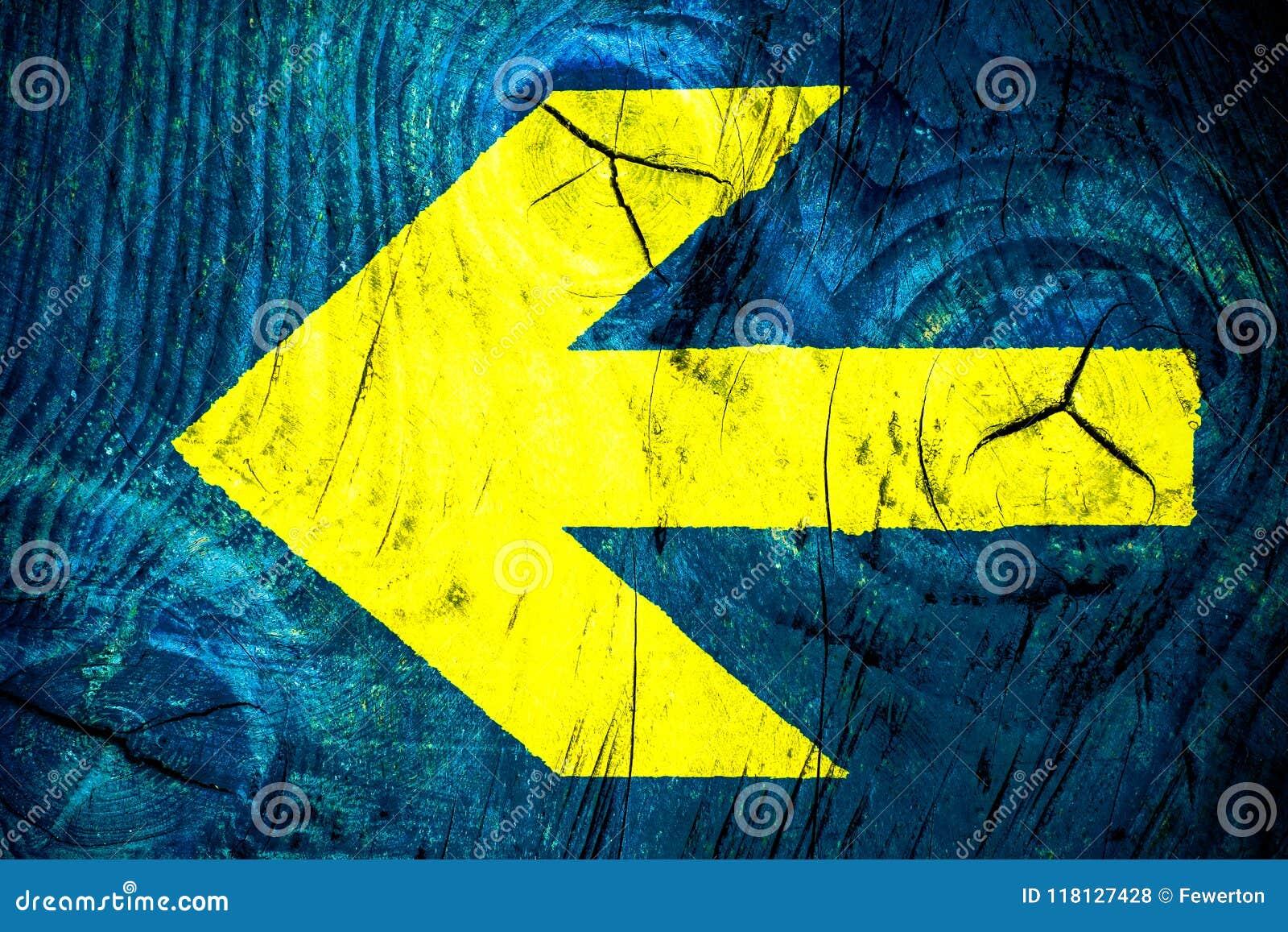 La direction jaune de flèche signal plus de le mur en bois de couleur bleue lumineuse vive avec des imperfections et les fissures