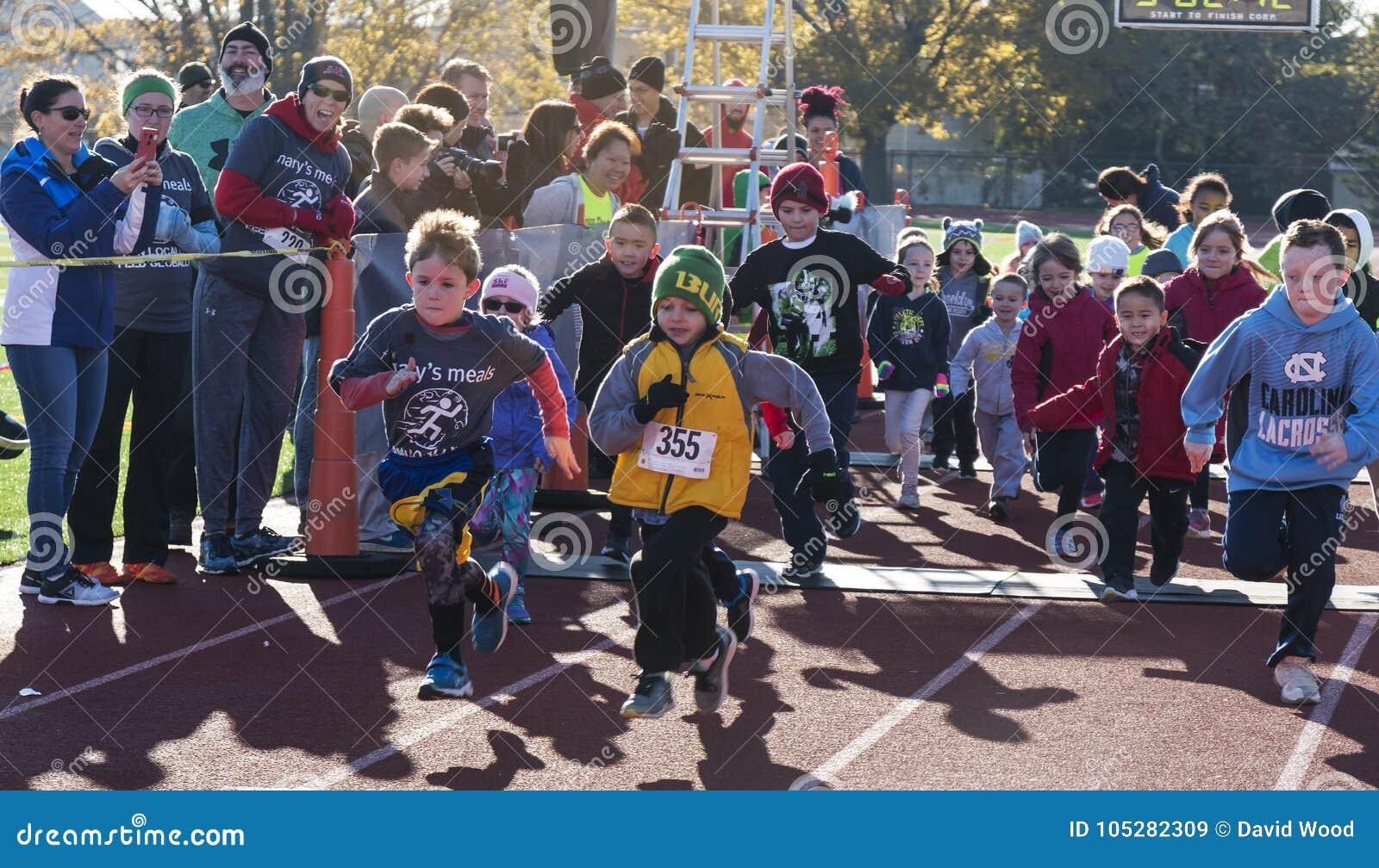 La diversión de los niños corre en una pista en una raza del trote de pavo