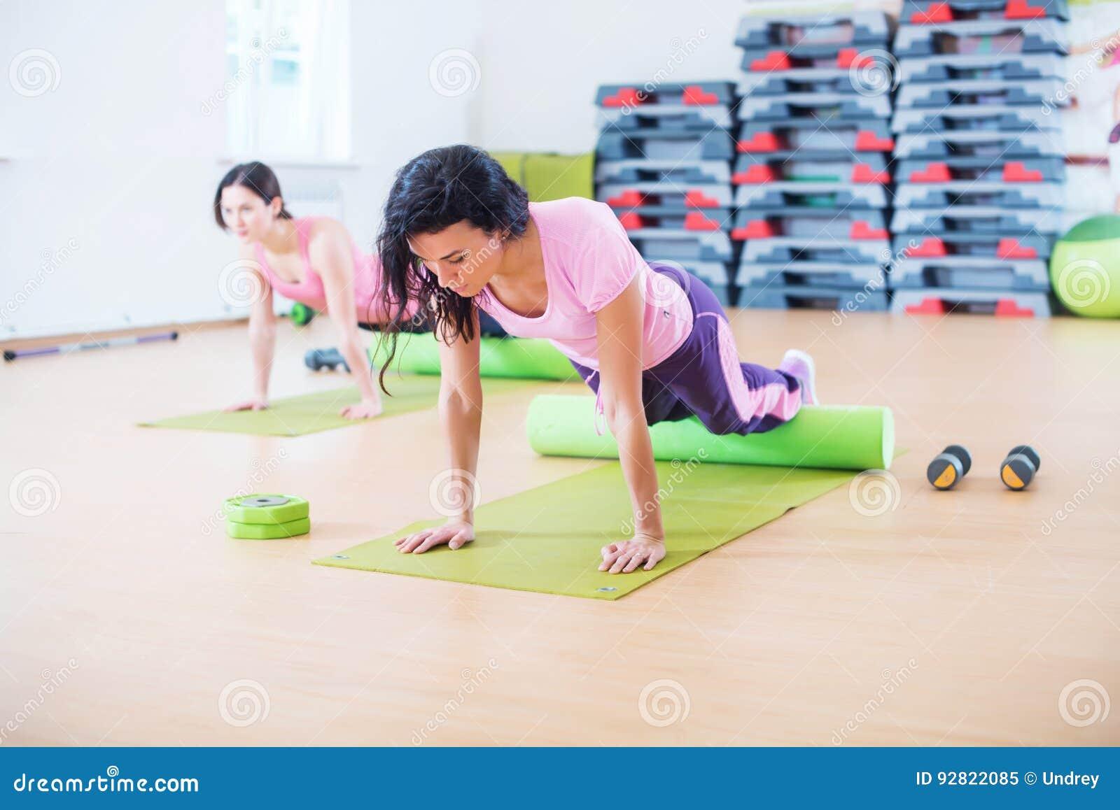 La donna adatta che fa i pilates esercita l allungamento incurvandola indietro allo studio di forma fisica