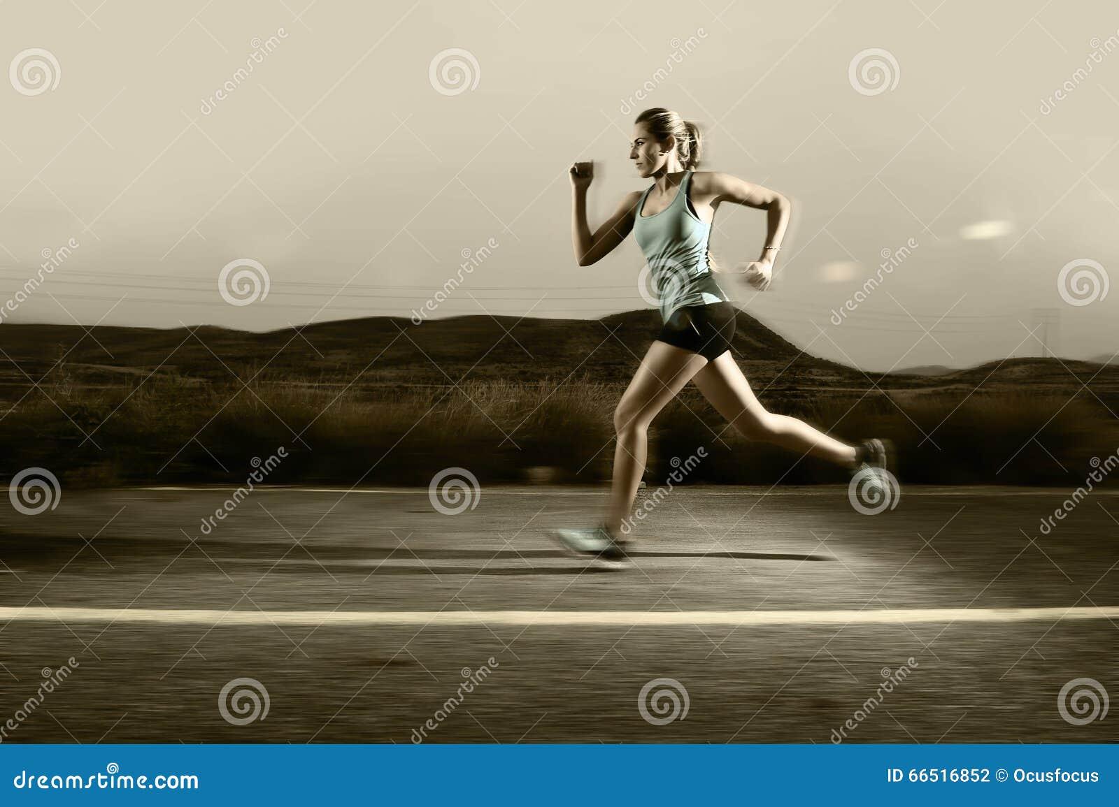 La donna adatta di sport dei giovani che corre all aperto sulla strada asfaltata nel paesaggio della montagna e nella luce dramma