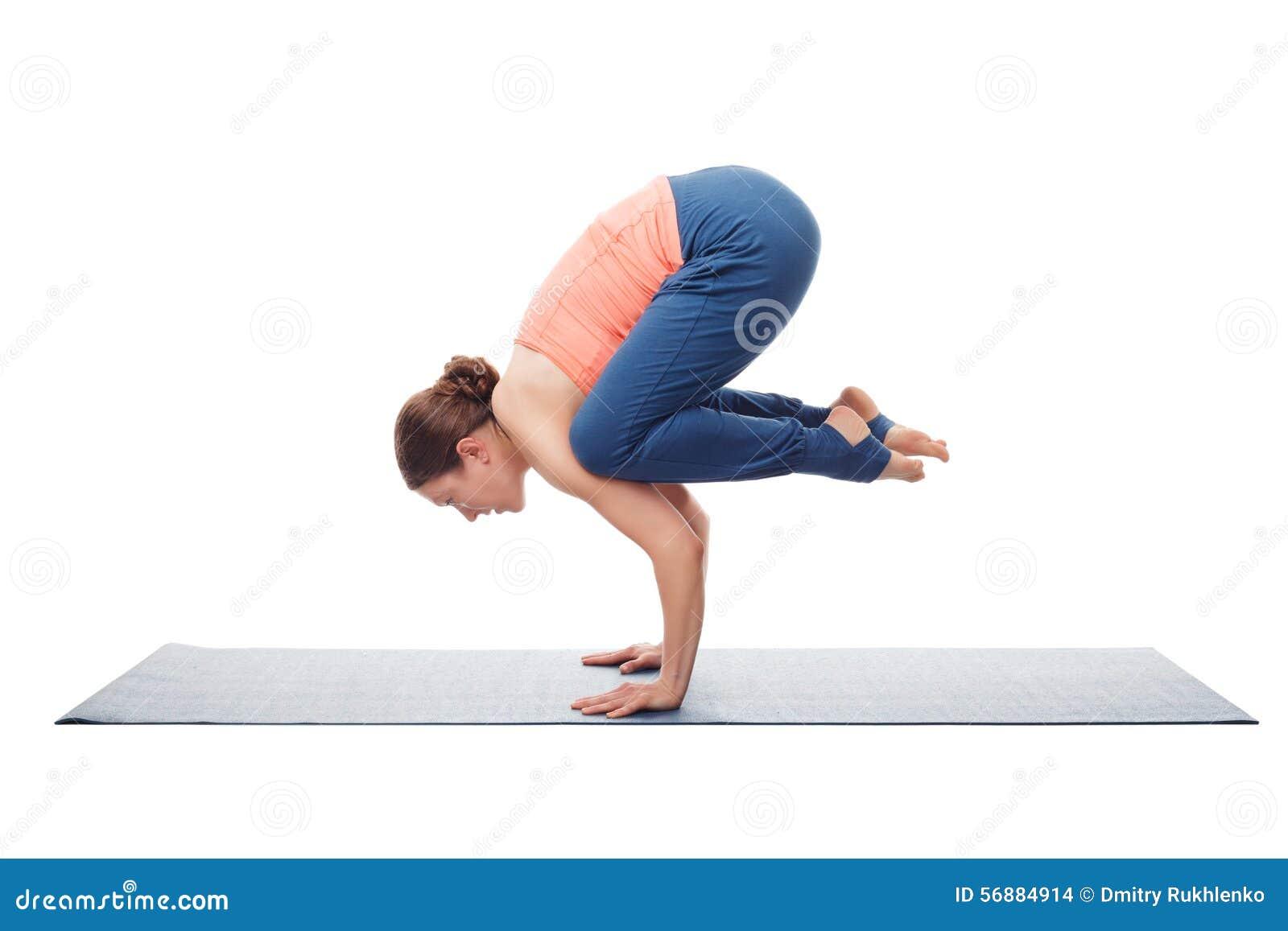 La donna adatta di yogini pratica il asana Bakasana di yoga