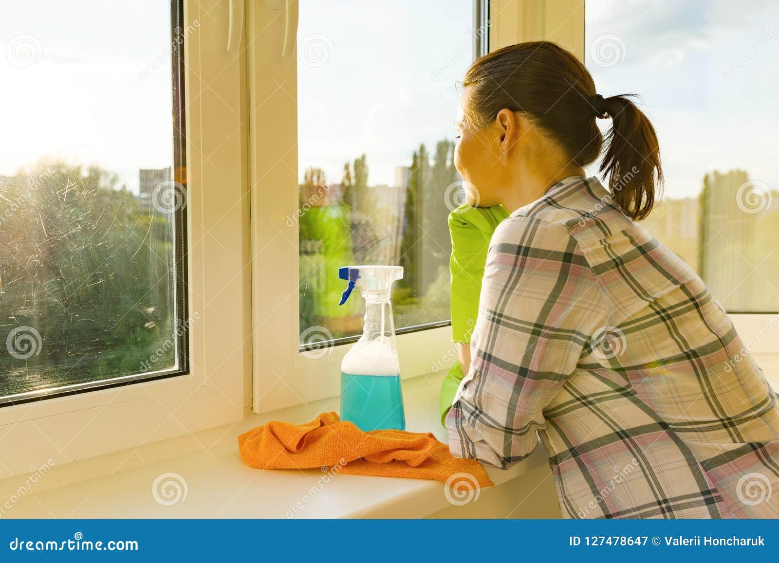 La donna adulta lava le finestre, pulenti la casa, femmina esamina una finestra lavata pulita