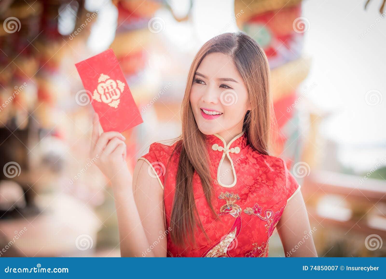 La donna asiatica in cinese veste il distico della tenuta  felice  (cinese w