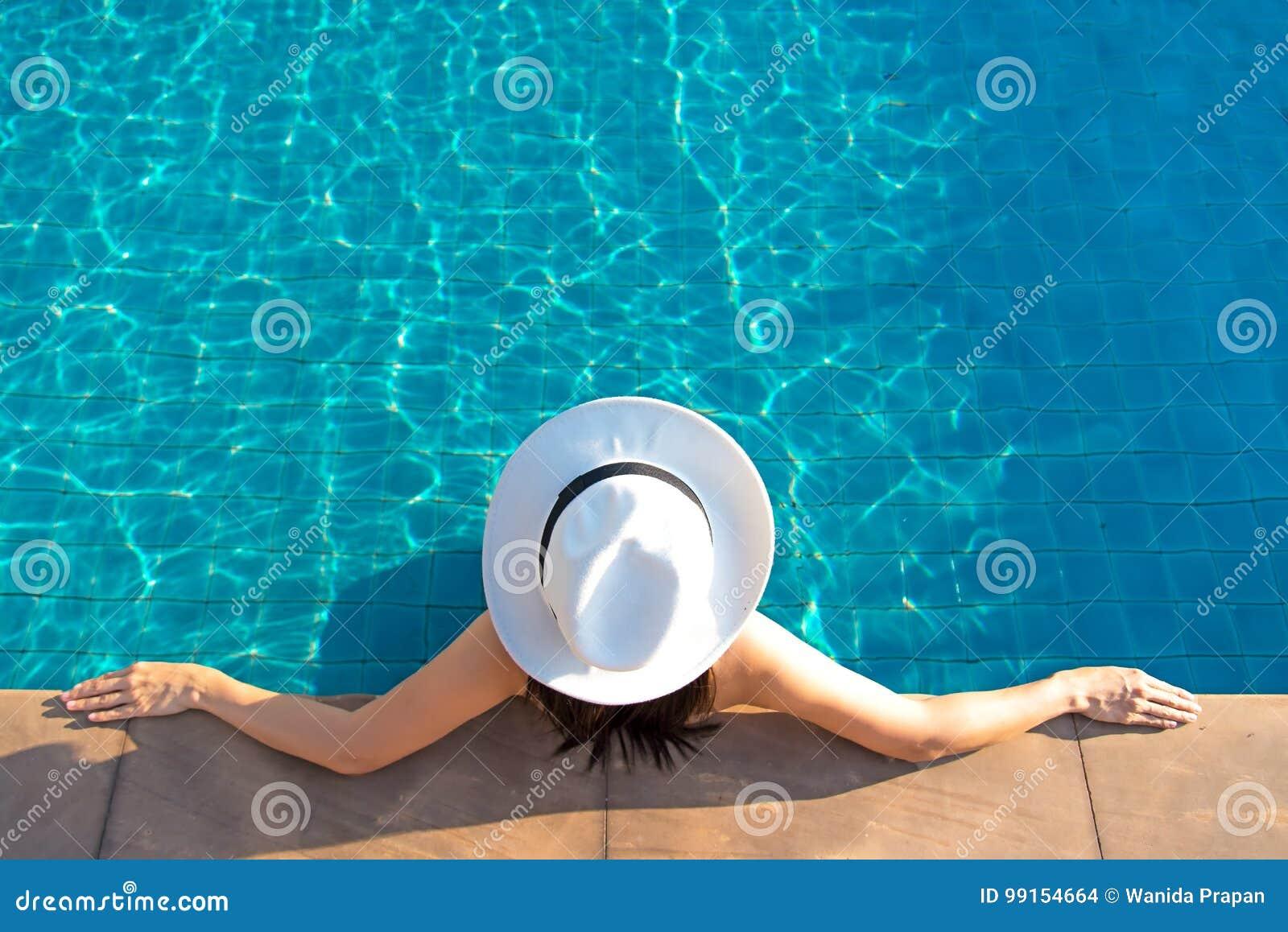 La donna asiatica sorridente felice con il cappello di paglia si rilassa e lusso nella piscina all hotel di località di soggiorno