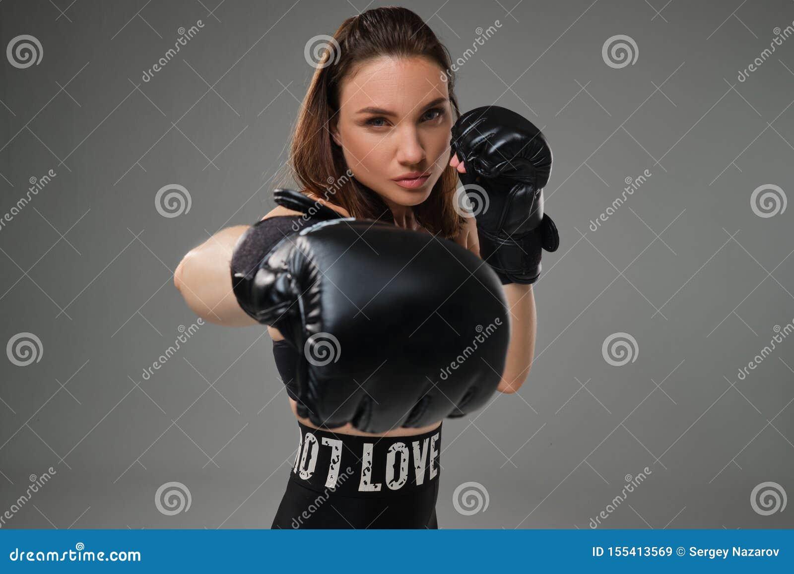 La donna atletica in guantoni da pugile sta praticando il karatè in studio