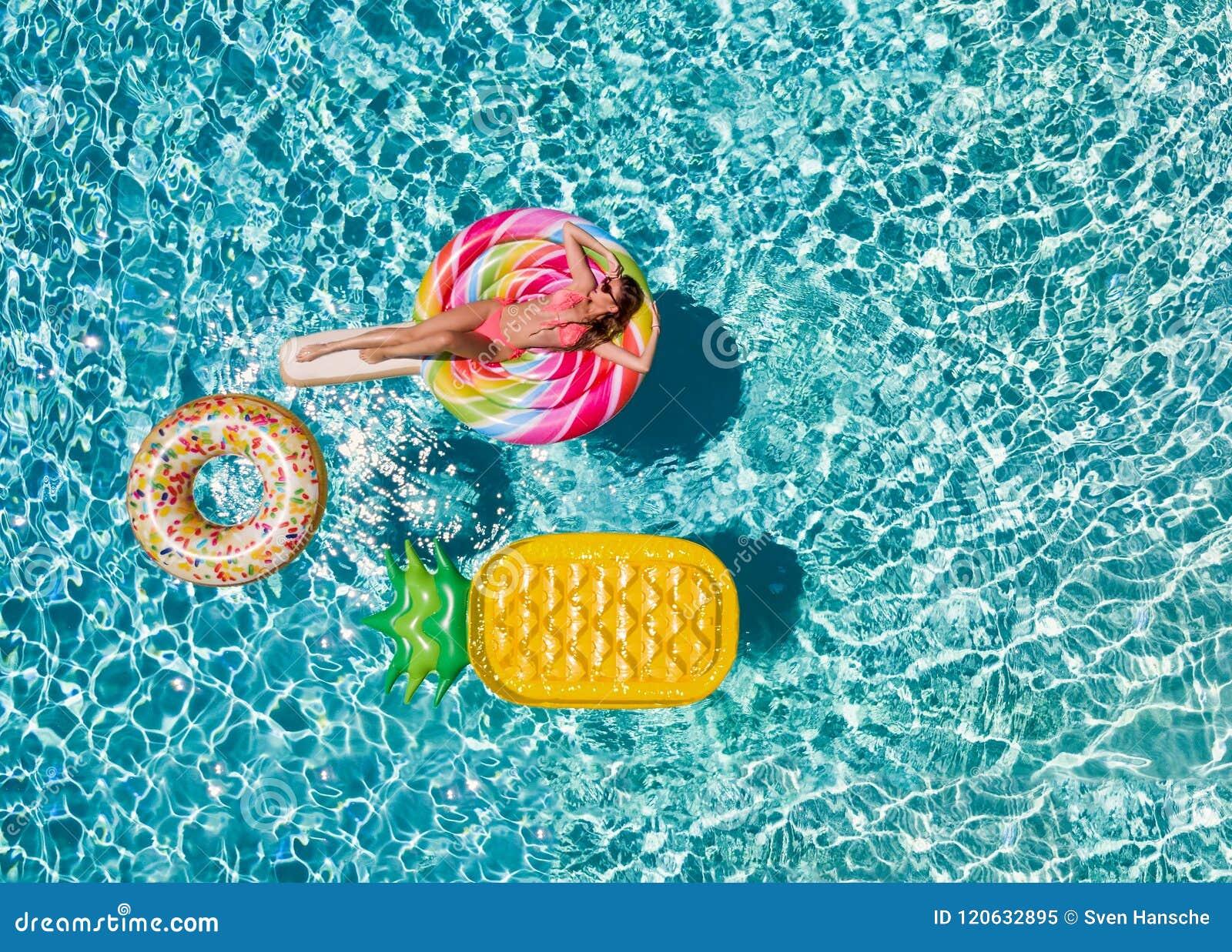 La donna in bikini si rilassa su un galleggiante della piscina a forma di schiocco di lolli