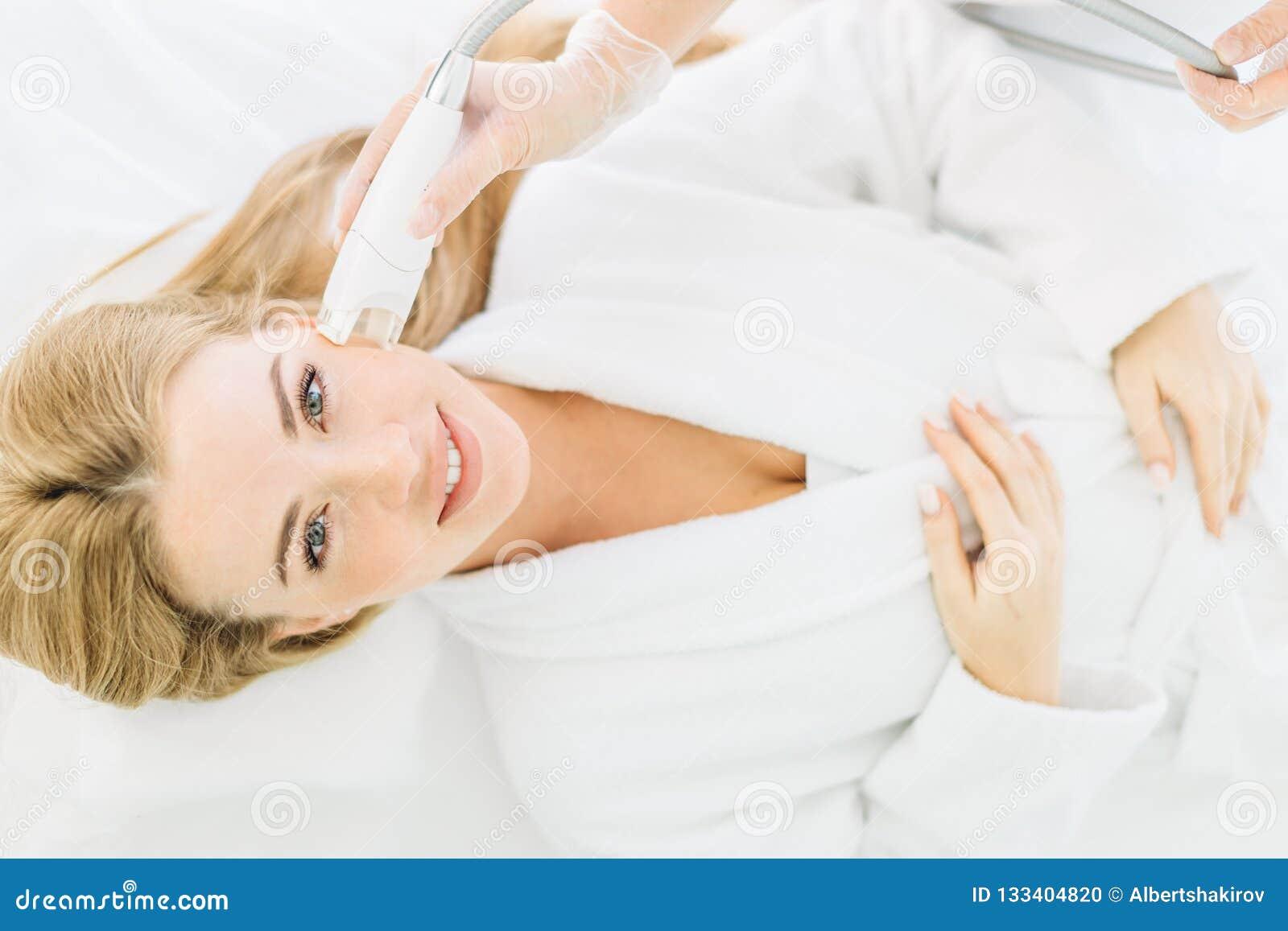 La donna bionda con capelli lunghi fa il laser del fronte che rifa la superficie al centro di bellezza