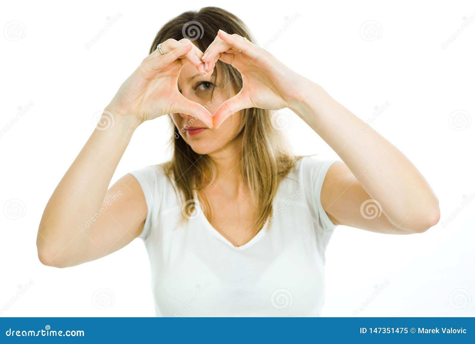 La donna bionda mostra la forma del cuore con le mani - guardando attraverso il cuore - simbolo di amore