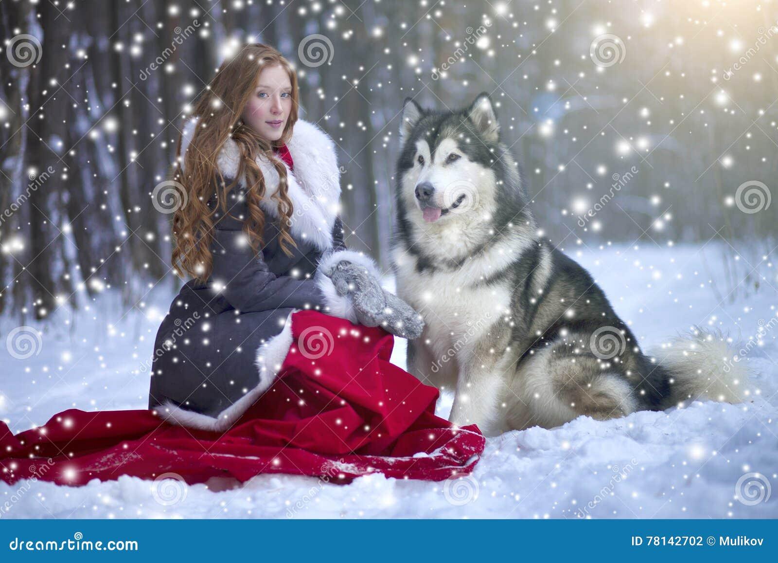 La donna in cappotto grigio con un cane o un lupo