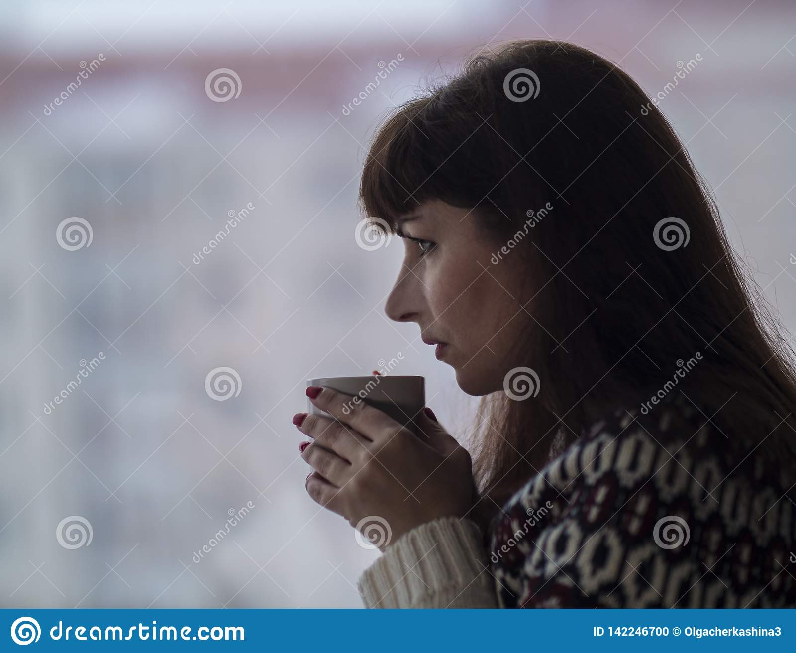 La donna castana beve il caffè e guarda fuori la finestra meditatamente