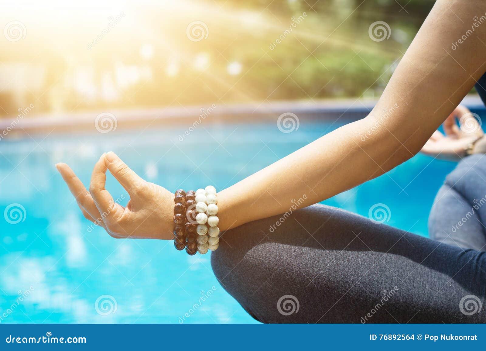 La donna che medita con il polso borda in una posizione di yoga del loto al bl