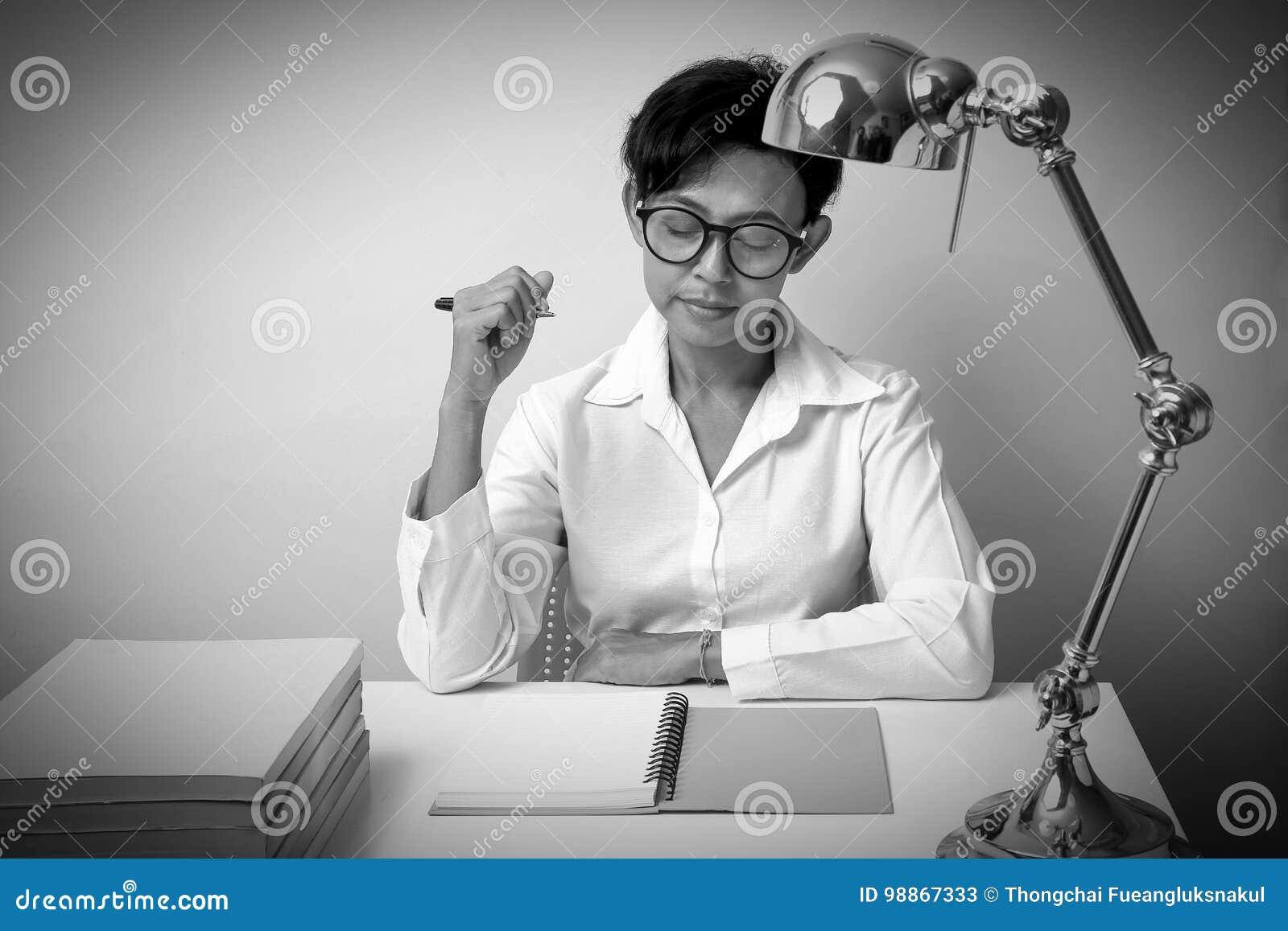 La donna che pensa e fa disporre una penna e un blocco note