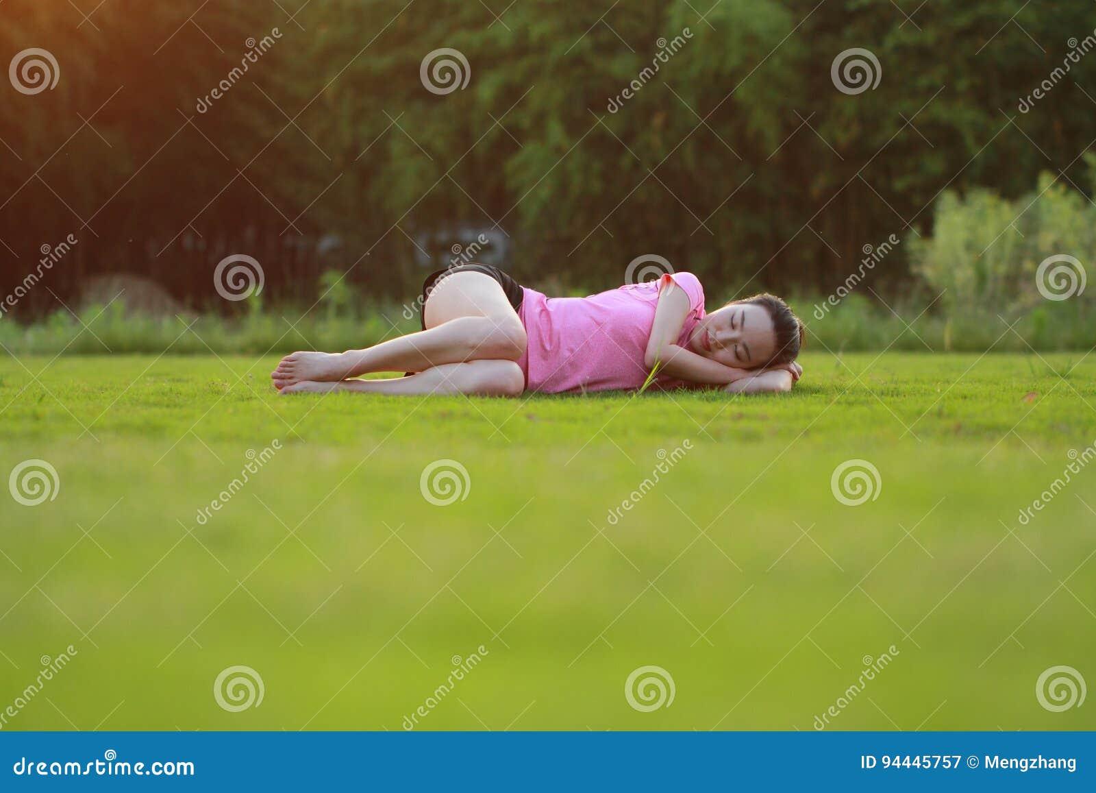 La donna cinese asiatica felice si rilassa su erba