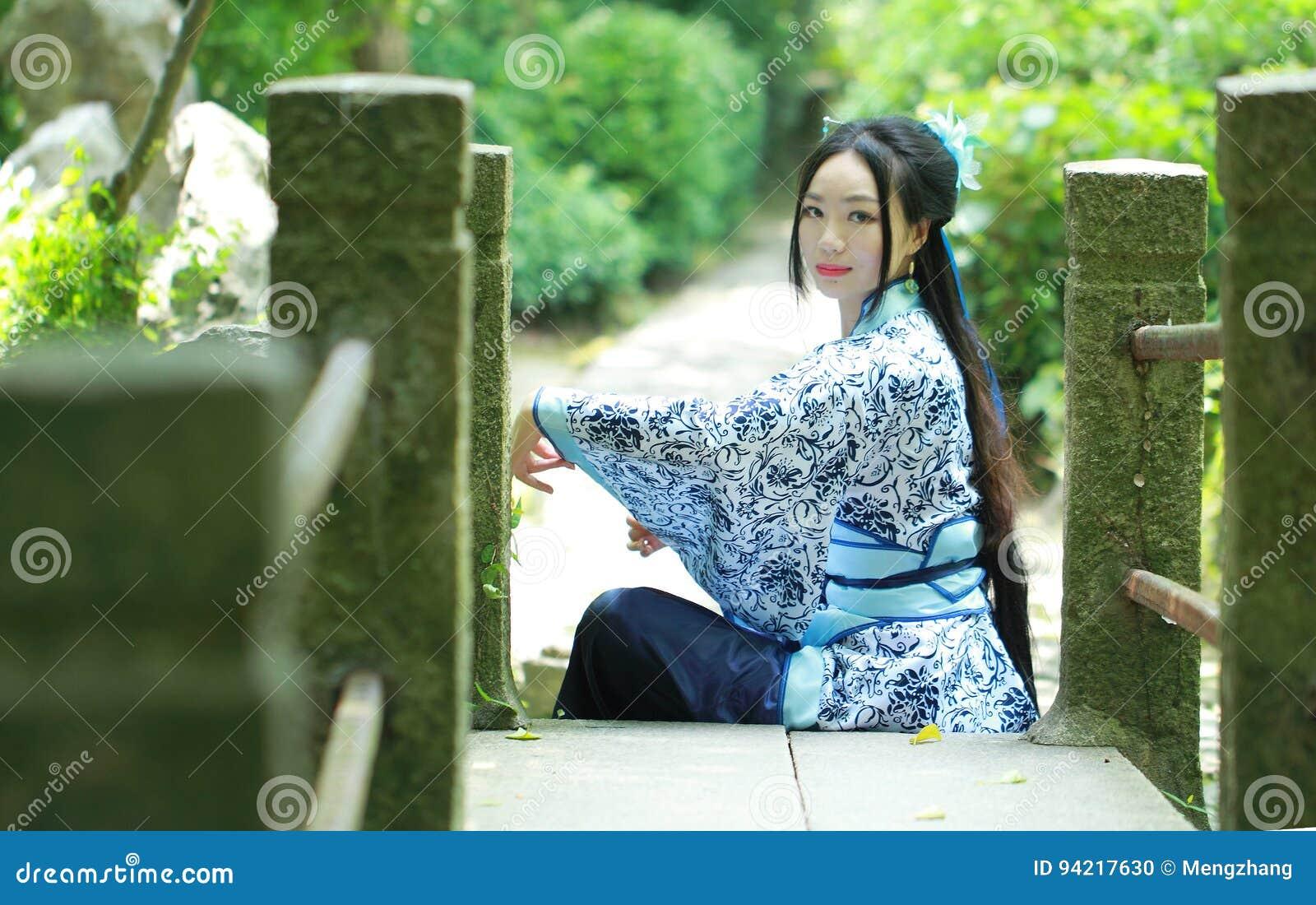 La donna cinese asiatica in vestito blu e bianco tradizionale da Hanfu, gioco in un giardino famoso, si siede sul ponte