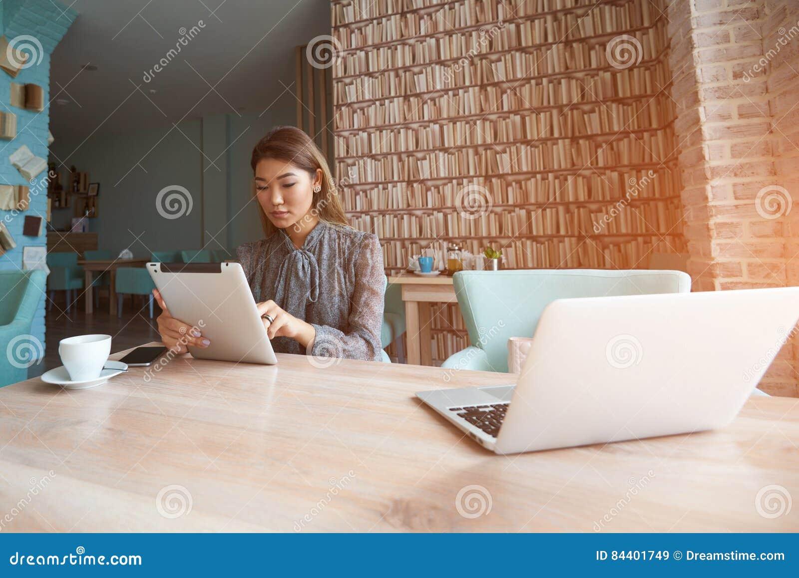 La donna cinese attraente sta utilizzando il computer portatile