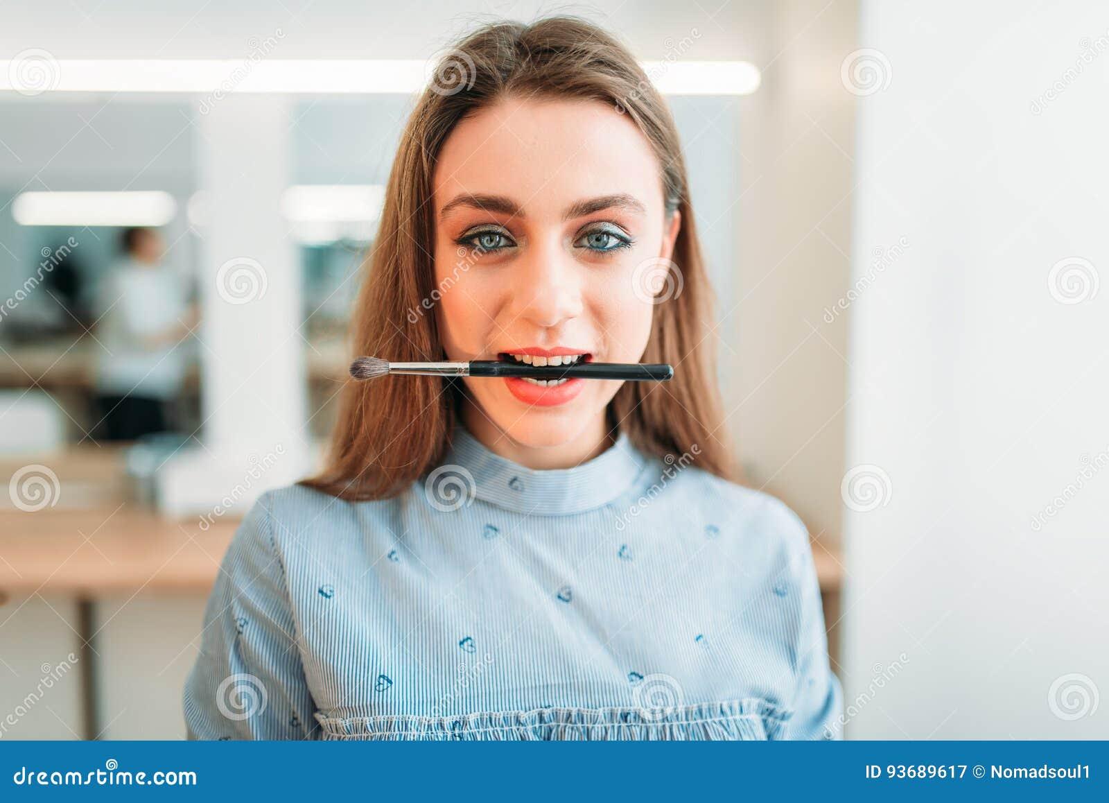 La donna con la spazzola in denti posa nello studio di bellezza