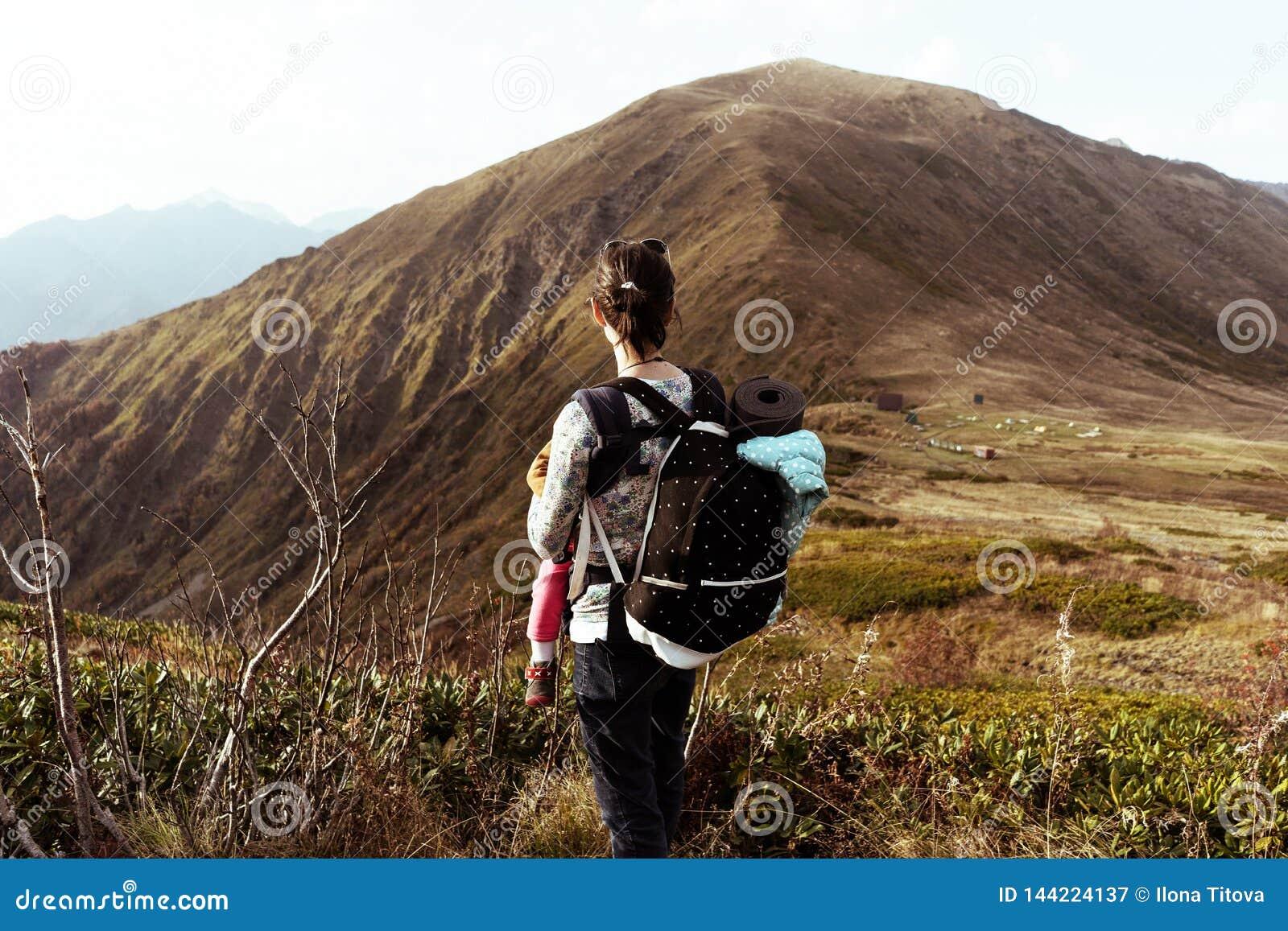 La donna con uno zaino nelle montagne è una retrovisione
