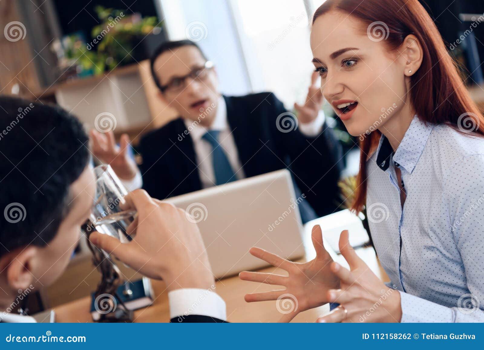 La donna dai capelli rossi sveglia grida all uomo, bicchiere dell acqua nell ufficio del ` s dell avvocato per il divorzio