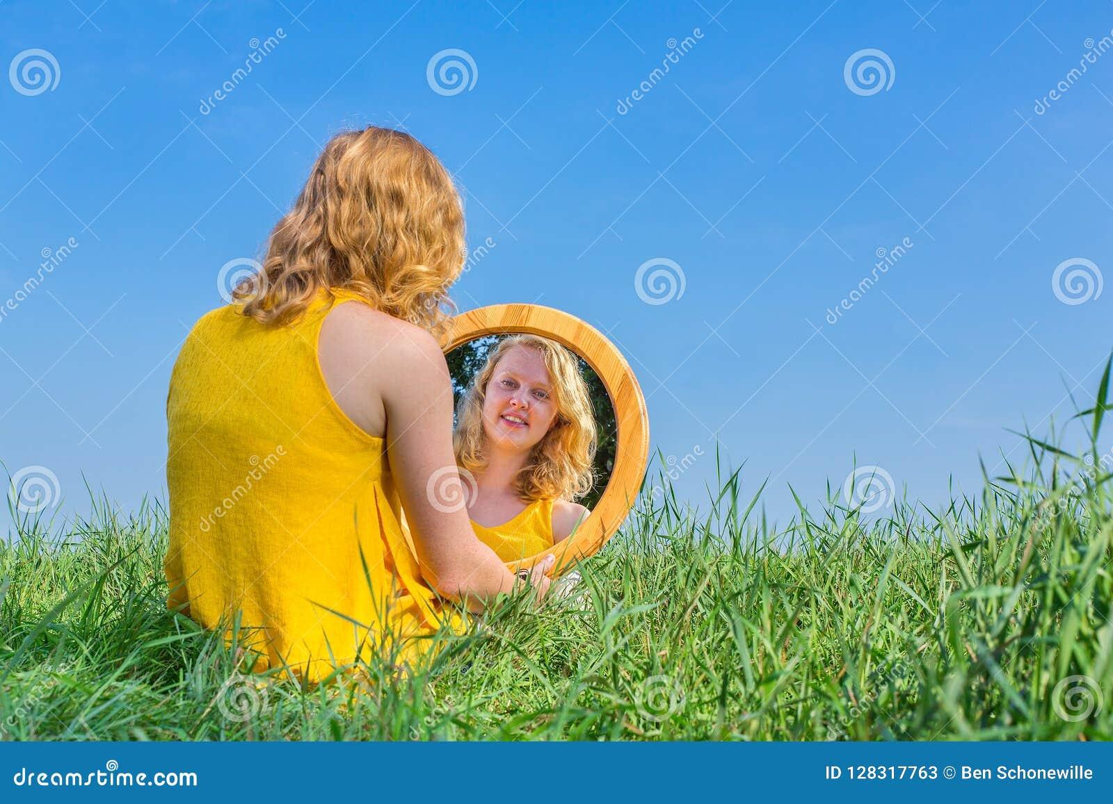 La donna della testarossa si siede esaminando lo specchio fuori