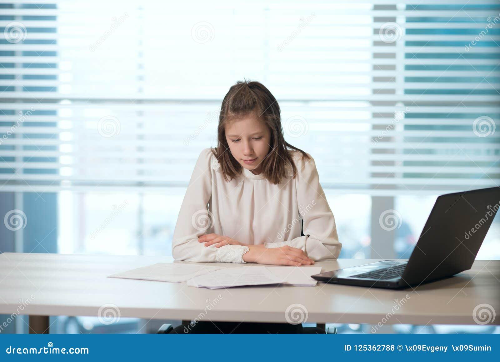La donna di affari della ragazza in abbigliamento casual, sedentesi ad una tavola esamina molto attentamente i documenti, lavoran