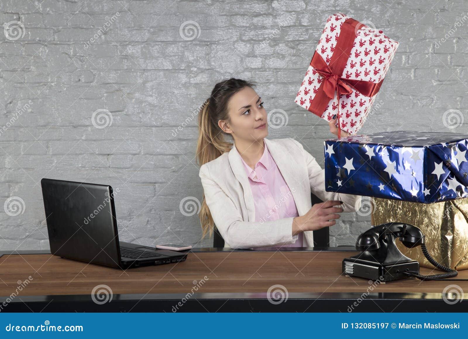 La donna di affari mette i regali sopra a vicenda