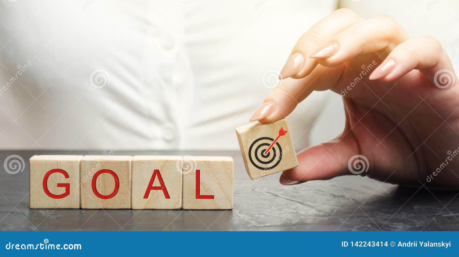La donna di affari tiene i blocchi di legno con lo scopo di parola Il concetto di raggiungimento degli scopi di affari Raggiungim