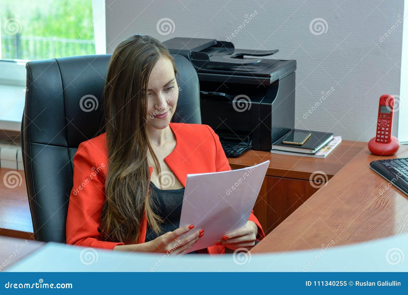 La donna di affari in vestito rosso si siede in una sedia di cuoio e nella lettura del contratto, controllante la carta