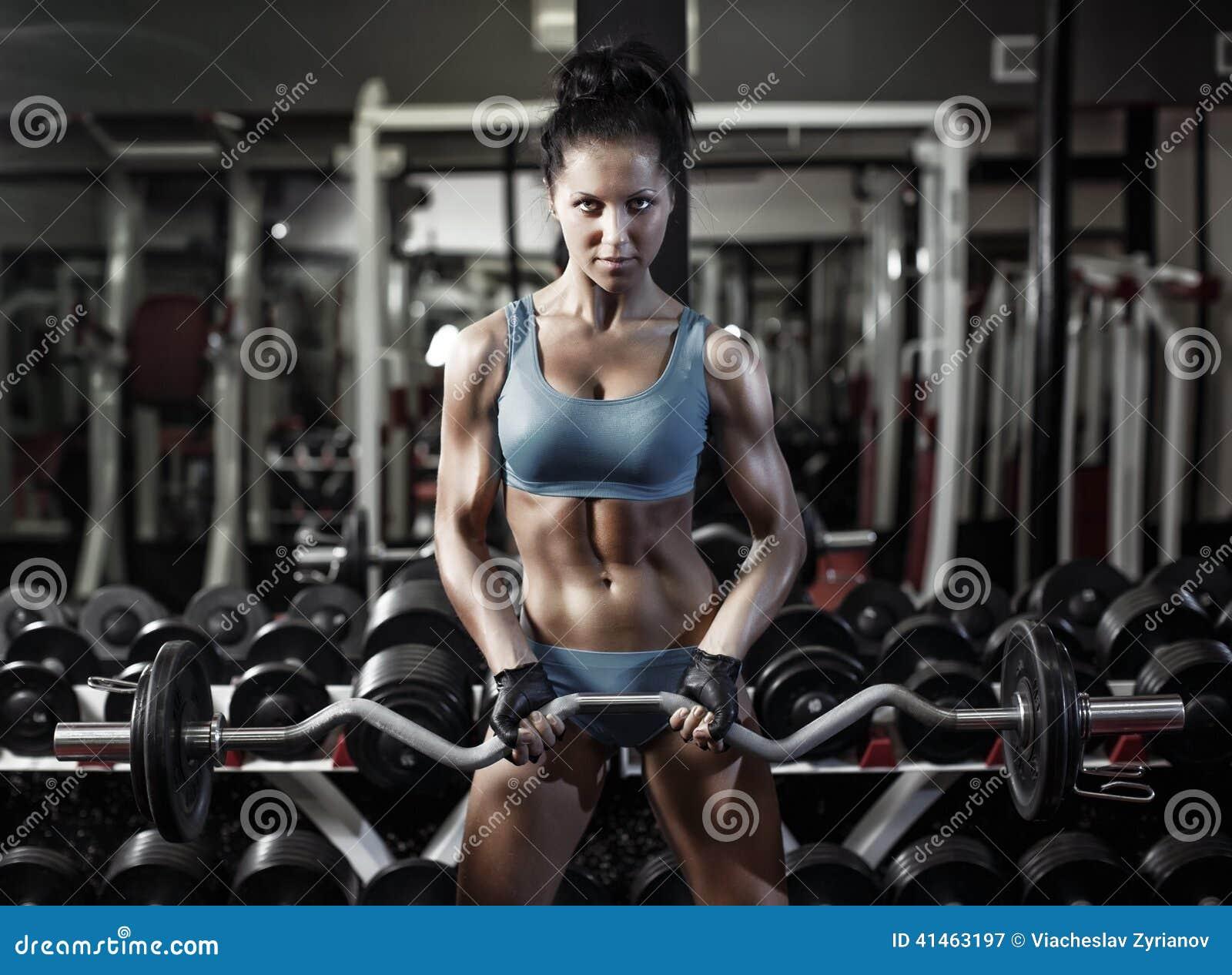 La donna di forma fisica spinge aumenta il bicipite con la testa di legno