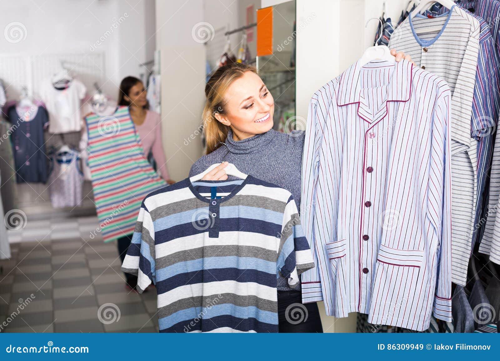 74daf91fee La donna divertente che sceglie i pigiami completa per l uomo in negozio