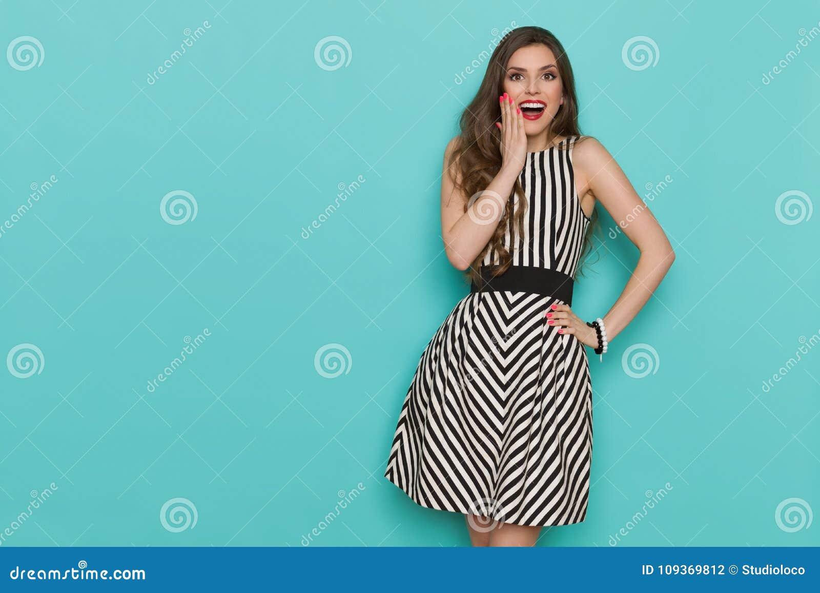 ee1091cd49ea La bella giovane donna sorpresa in vestito da cocktail stroped in bianco e nero  elegante sta tenendo la mano sul mento