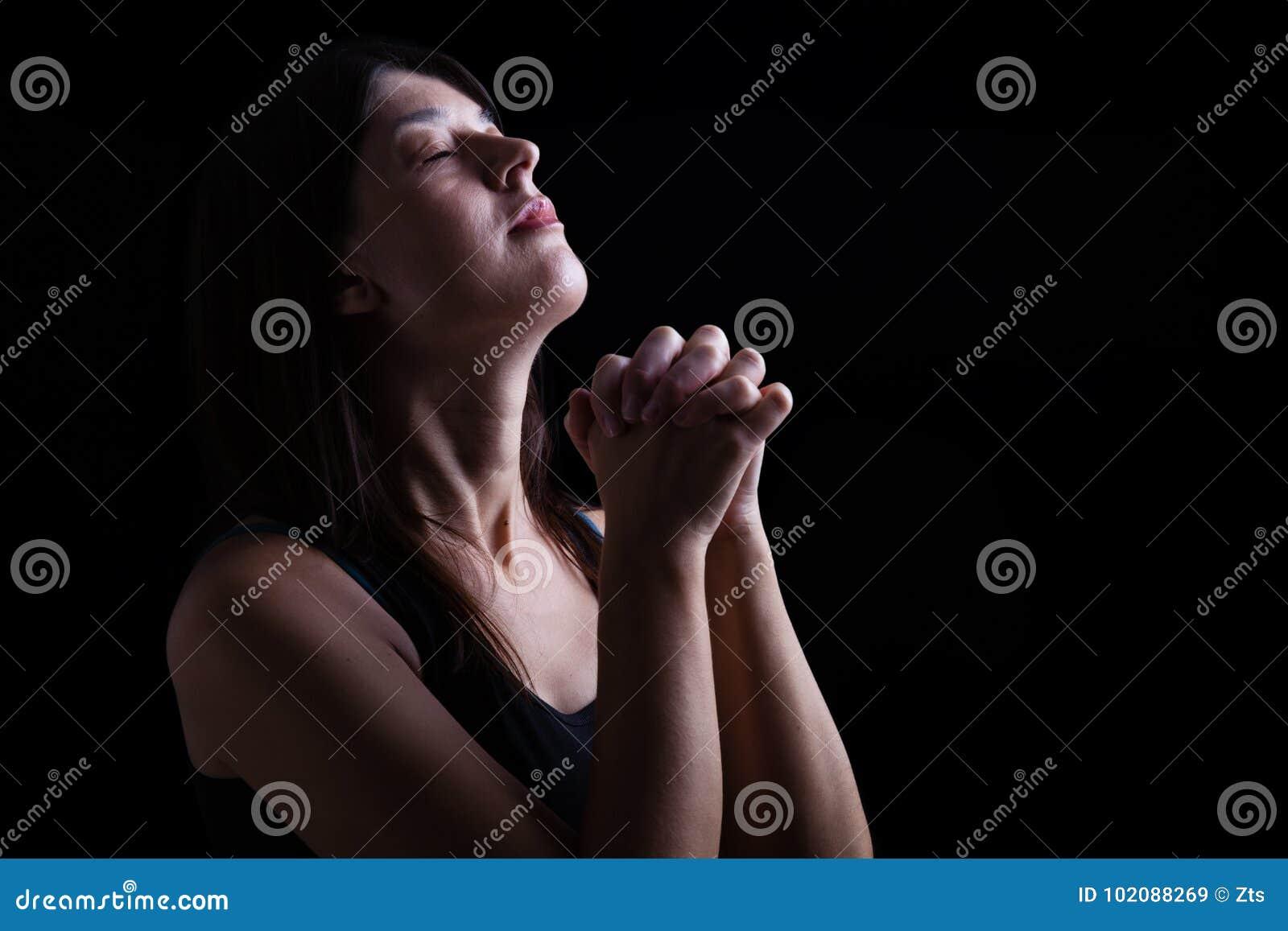 La donna fedele che prega, mani ha piegato nel culto