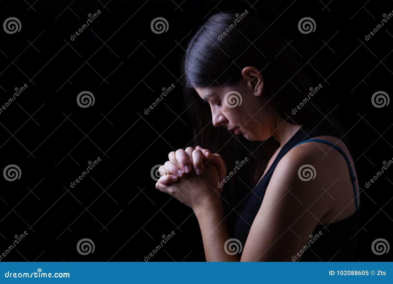 La donna fedele che prega, mani ha piegato nel culto al dio