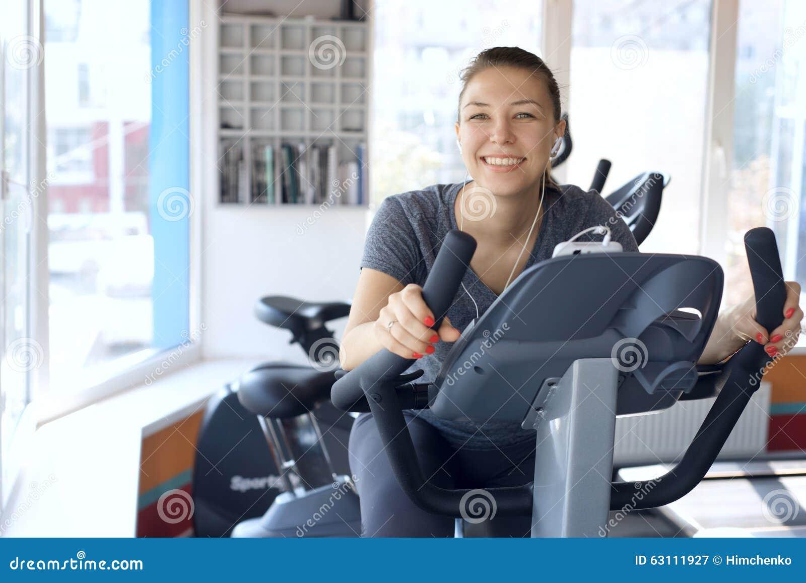 La donna felice è impegnata su una bici fissa