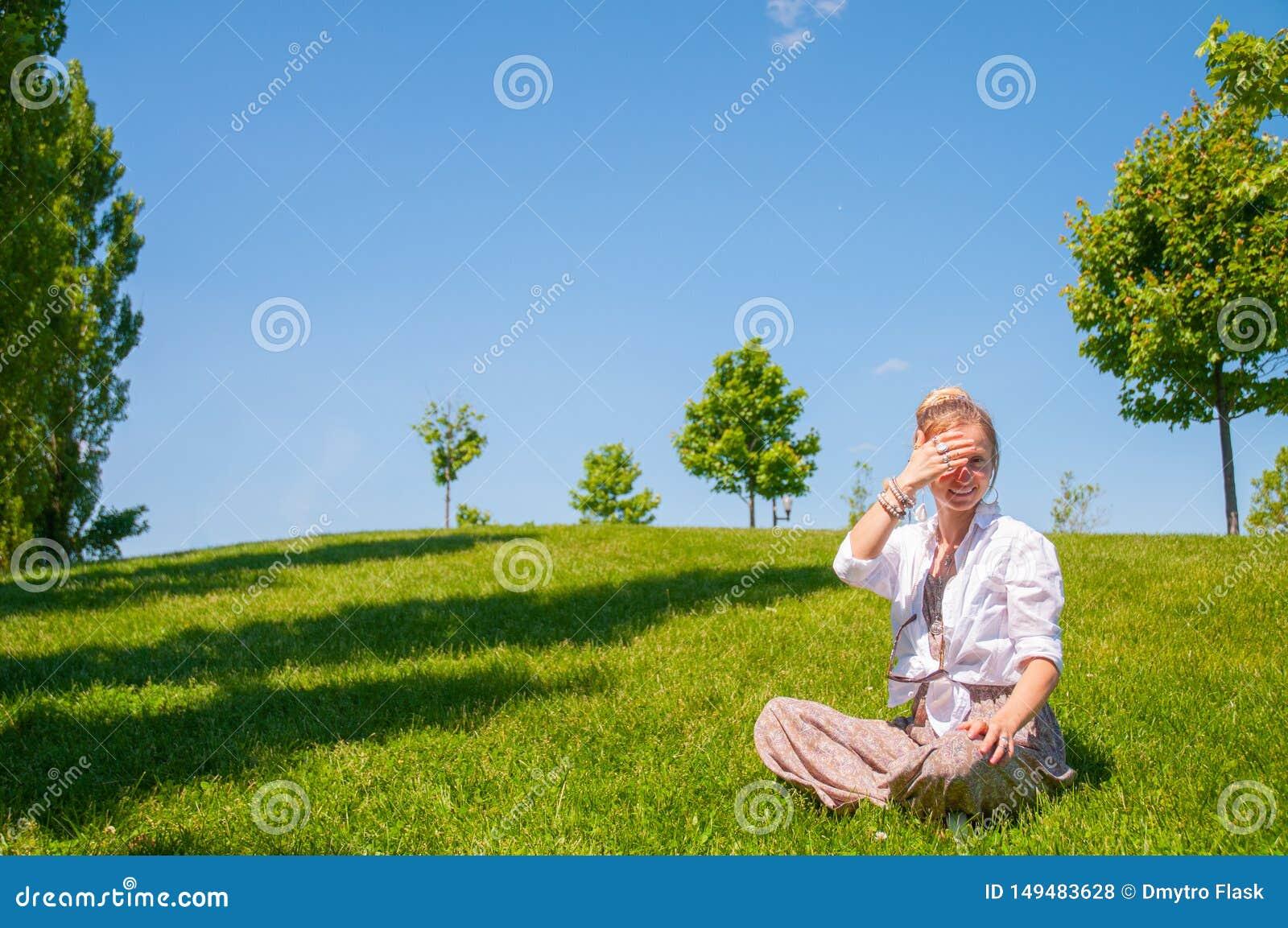 La donna felice sta sedendosi sul prato inglese dell erba La bella donna di stile di boho con gli accessori gode del giorno soleg