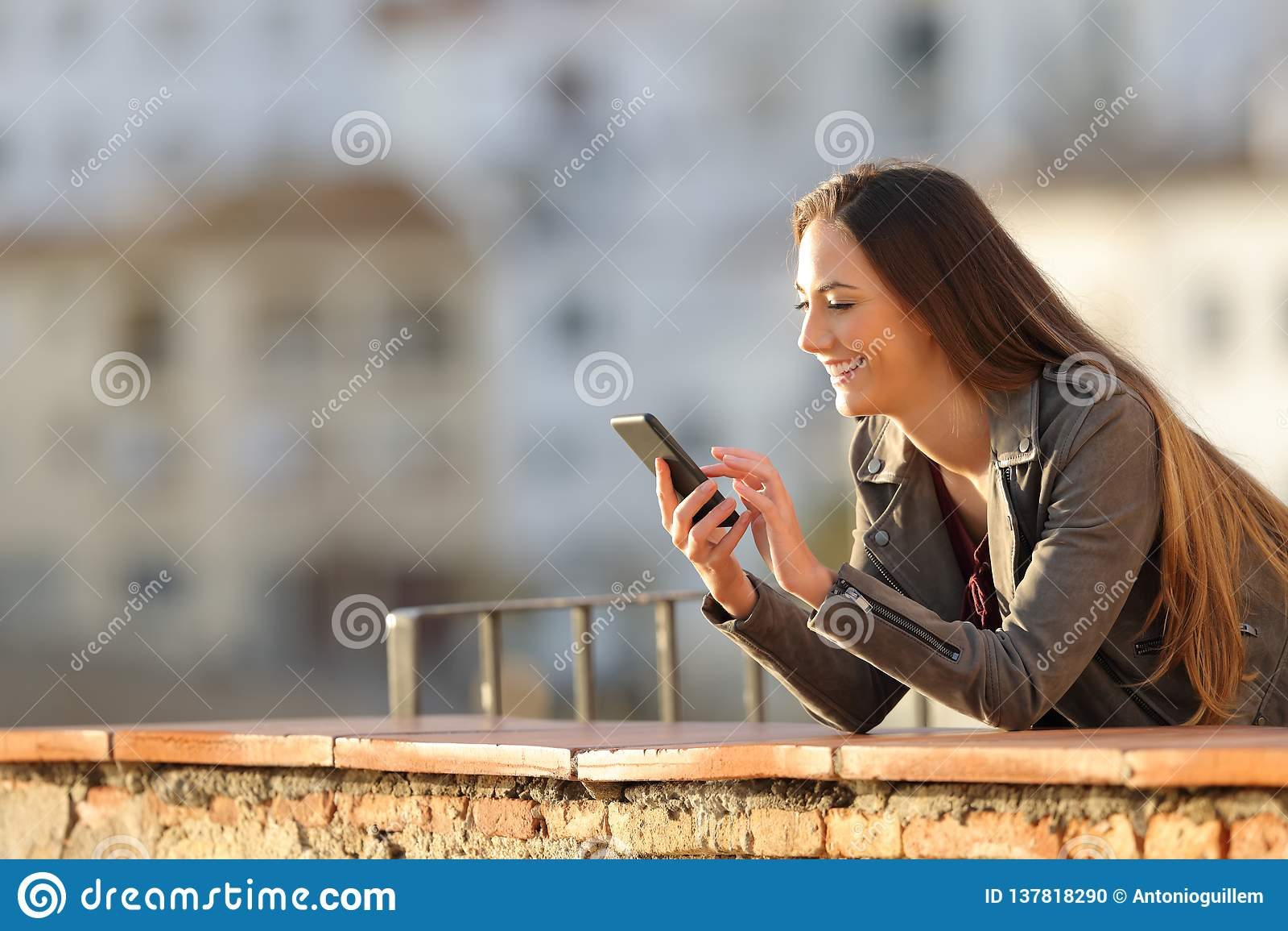 La donna felice utilizza uno Smart Phone in un balcone al tramonto