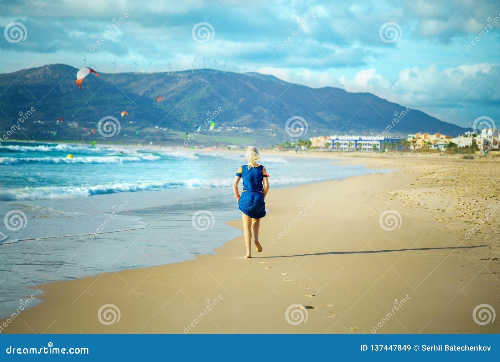 La donna funziona sulla spiaggia sabbiosa