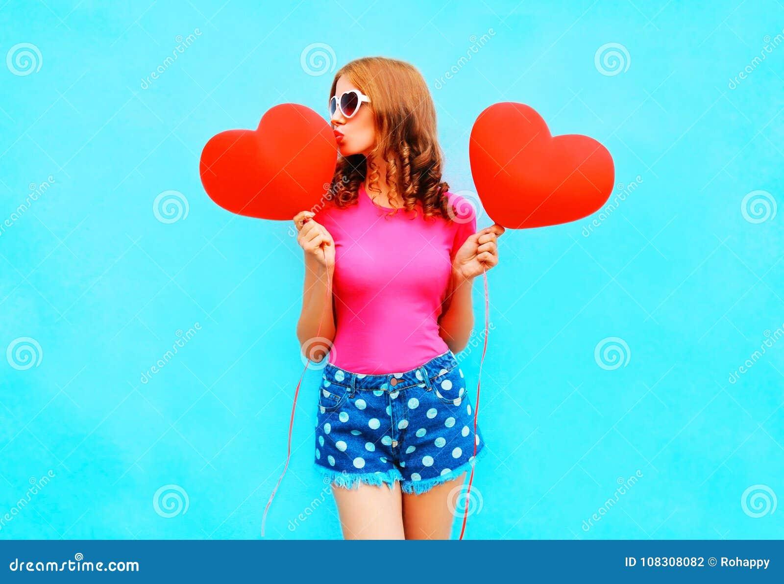 La donna graziosa bacia un pallone rosso sotto forma di cuore sul blu