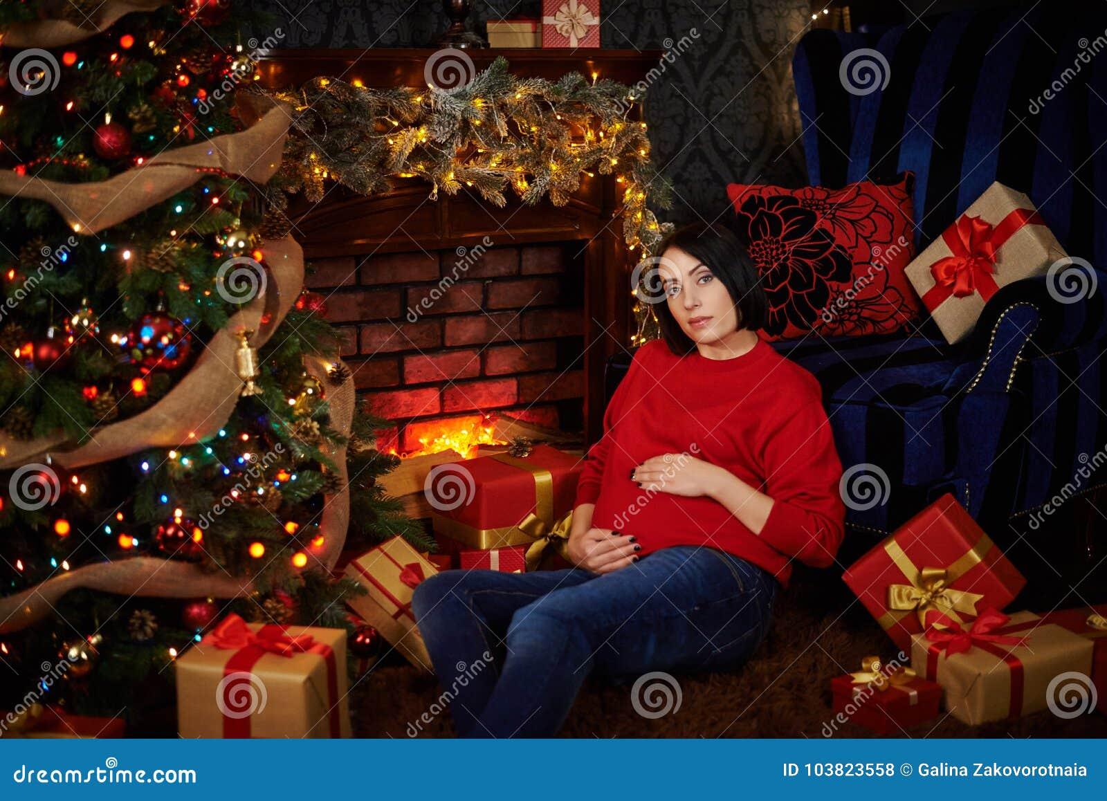 La donna incinta segna la sua pancia all albero di Natale