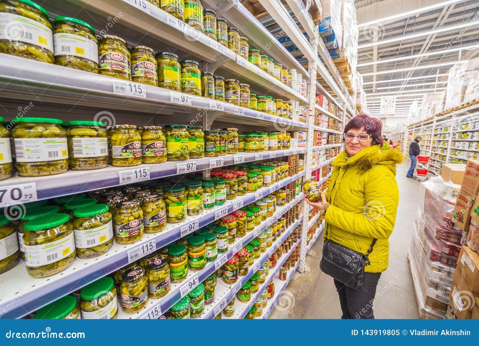 La donna matura sceglie le verdure inscatolate in un supermercato