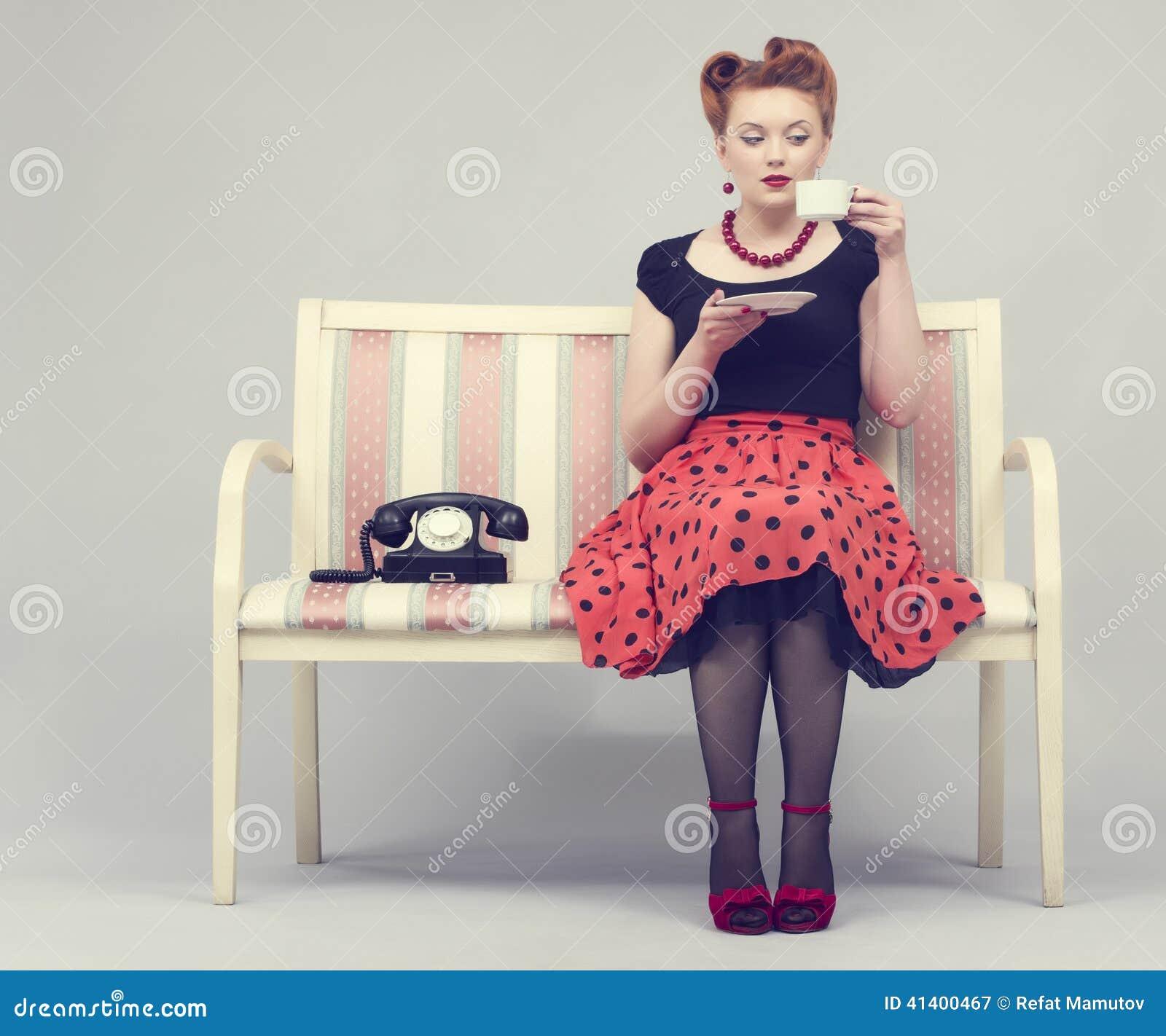 La donna nel retro stile beve il caffè che si siede sul