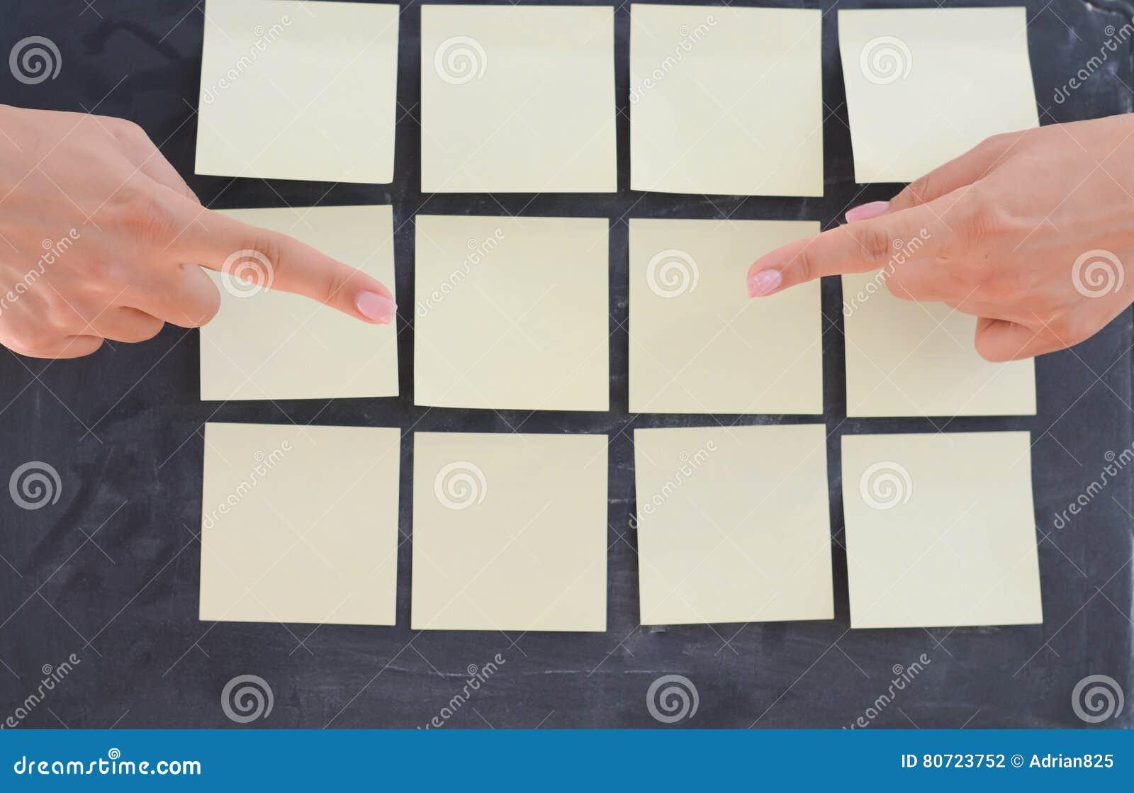 La donna passa l invio delle note adesive vuote sulla lavagna