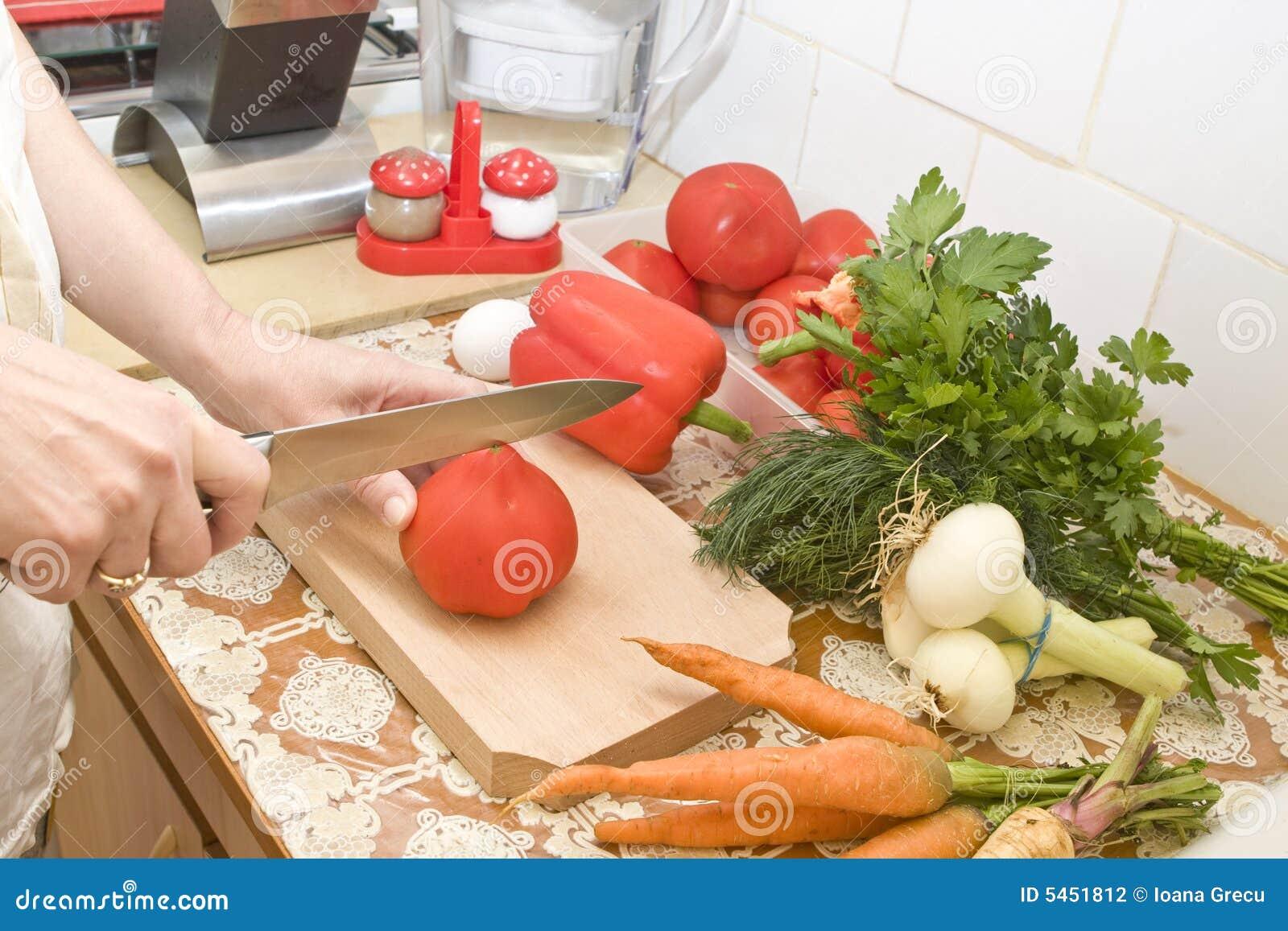 La donna passa a taglio il pomodoro maturo